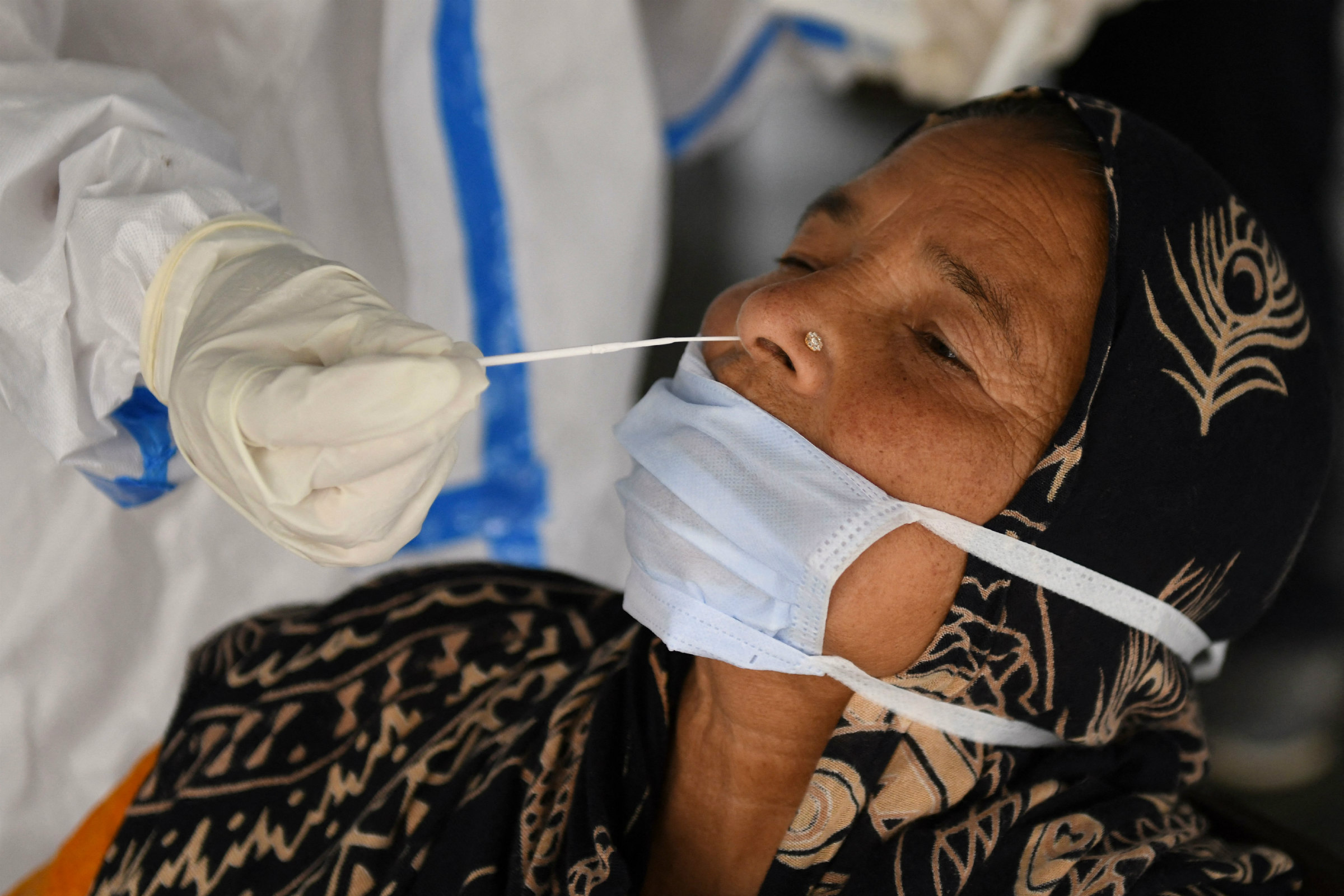 an Indian woman wearing a hijab leans her head back as a swab is stuck in her nostril