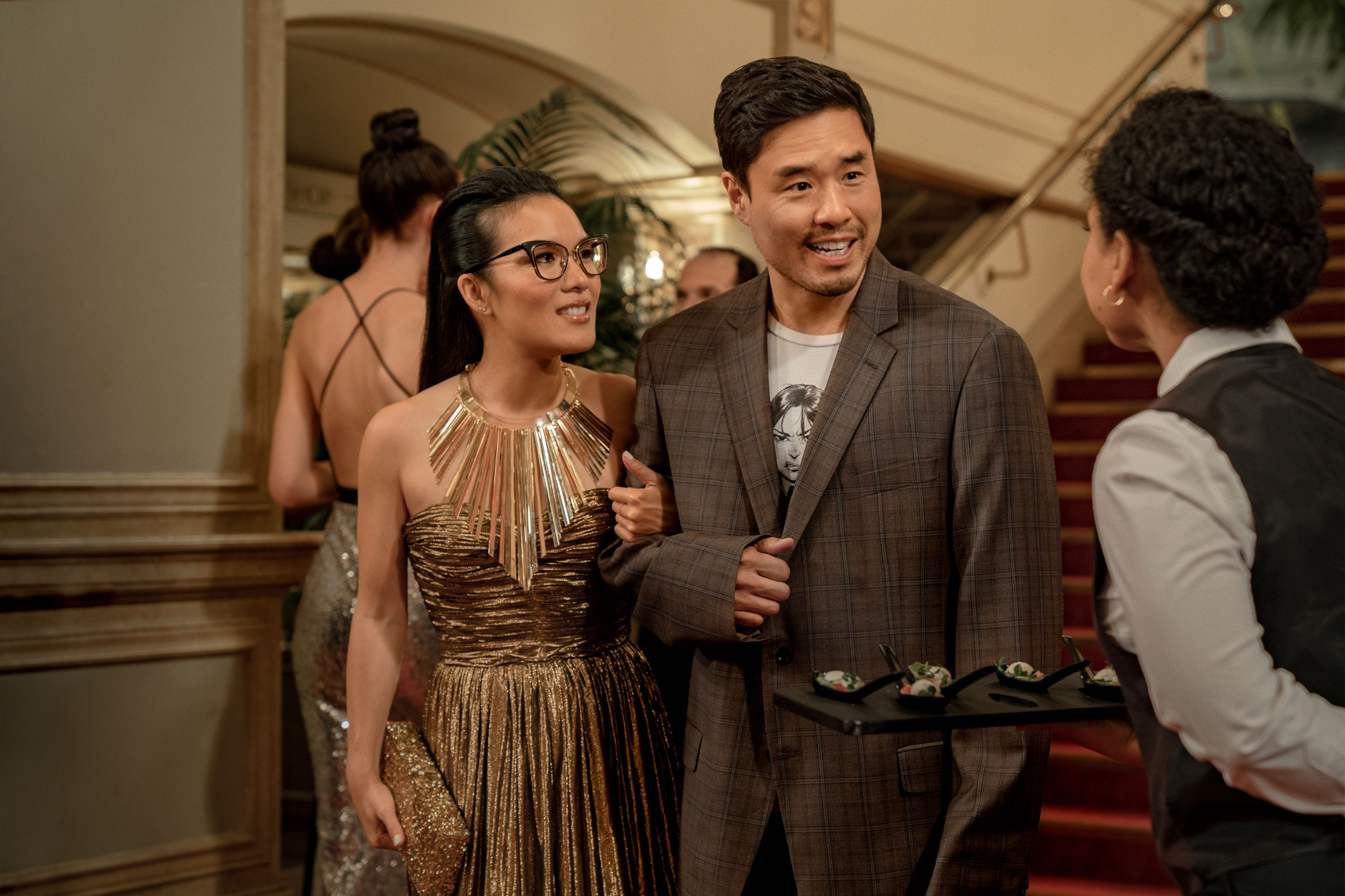 an Asian couple dressed in a gold dress and a tattered, checkered suit attend a gala together