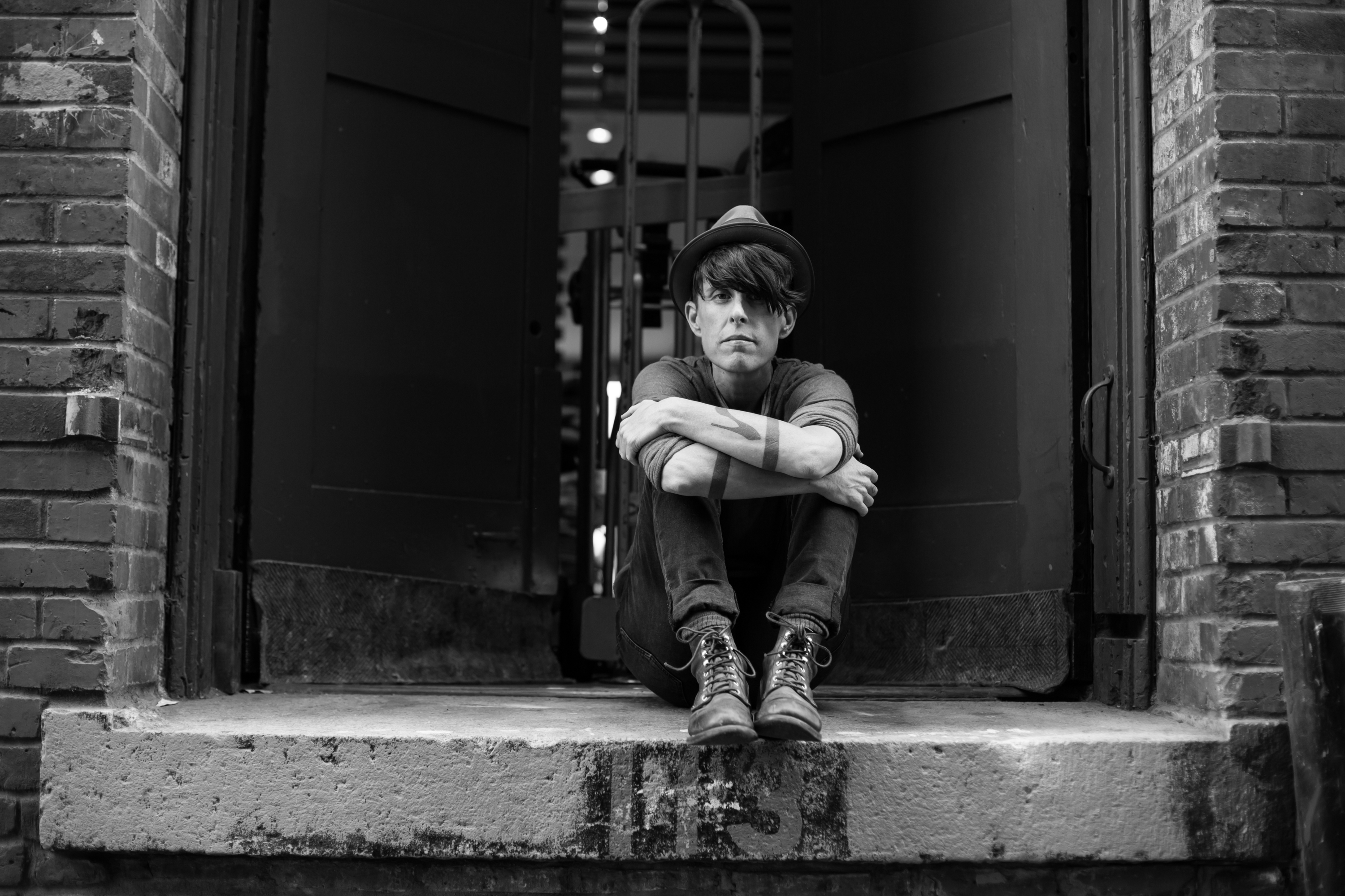 Andrea Gibson sits on a stoop