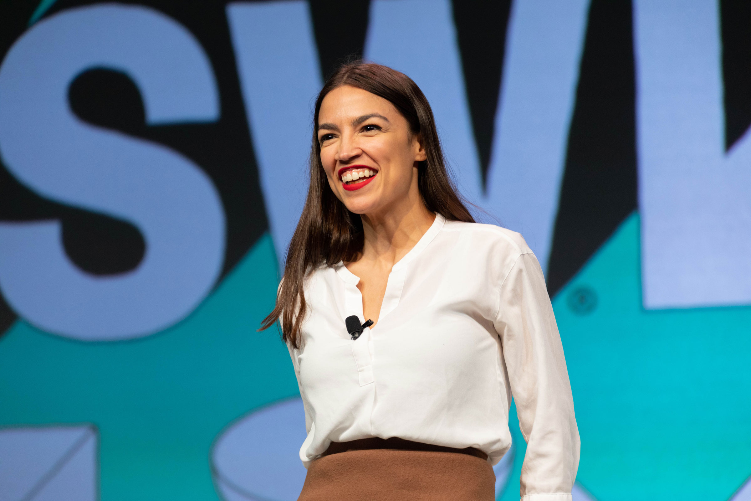 Alexandria Ocasio-Cortez smiles while standing on stage. She has long brown hair and wears red lipstick and a white blouse.