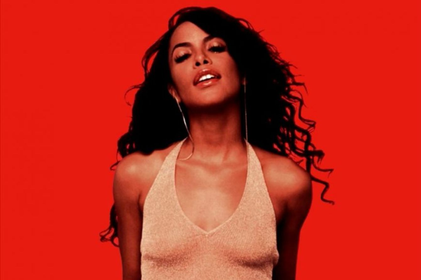Aaliyah, a thin, Black, woman with long, wavy Black hair poses against a red background as she stares directly at the camera