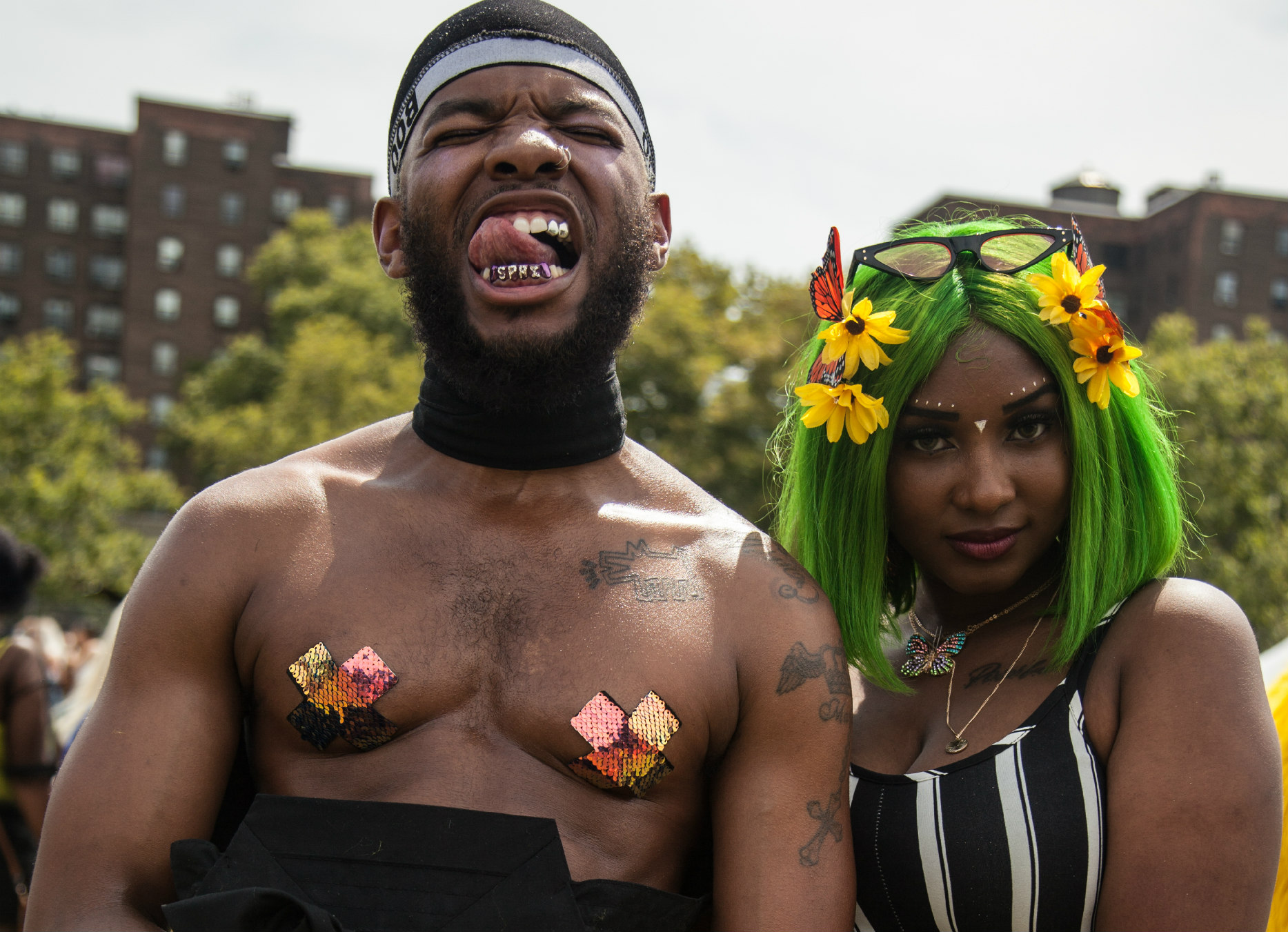 a brownskinned Black man with multicolored nipple covers, a gold grill, and his tongue licking his teeth standing next to a brownskinneed woman with green hair with yellow flowers and a striped black and white jumpsuit