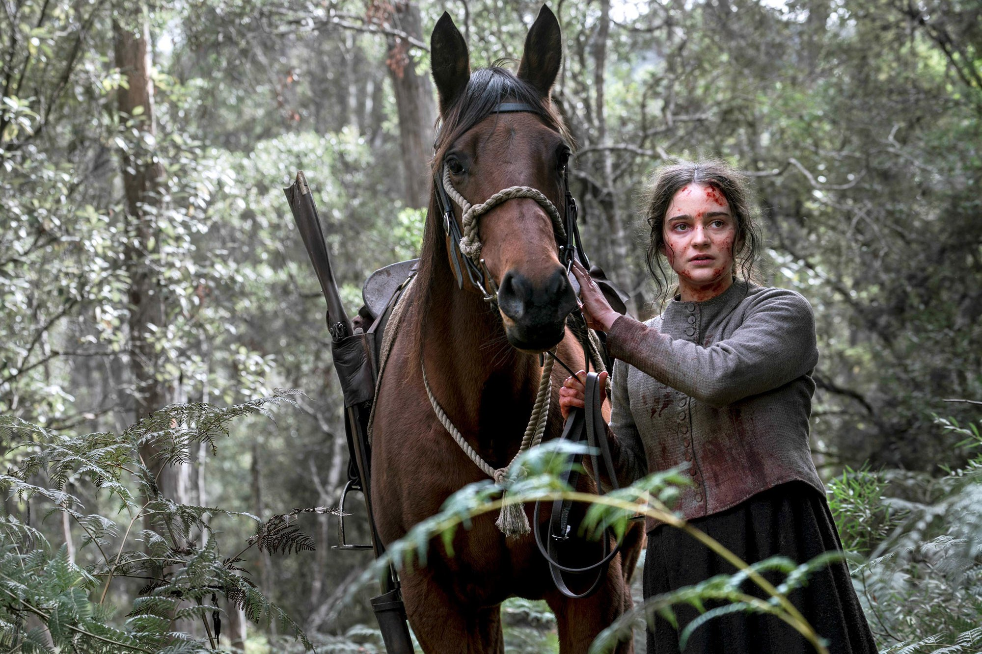 Aisling Franciosi, a white teenager with short, brown hair who's covered in blood and standing next to a brown horse, plays Clare in The Nightingale