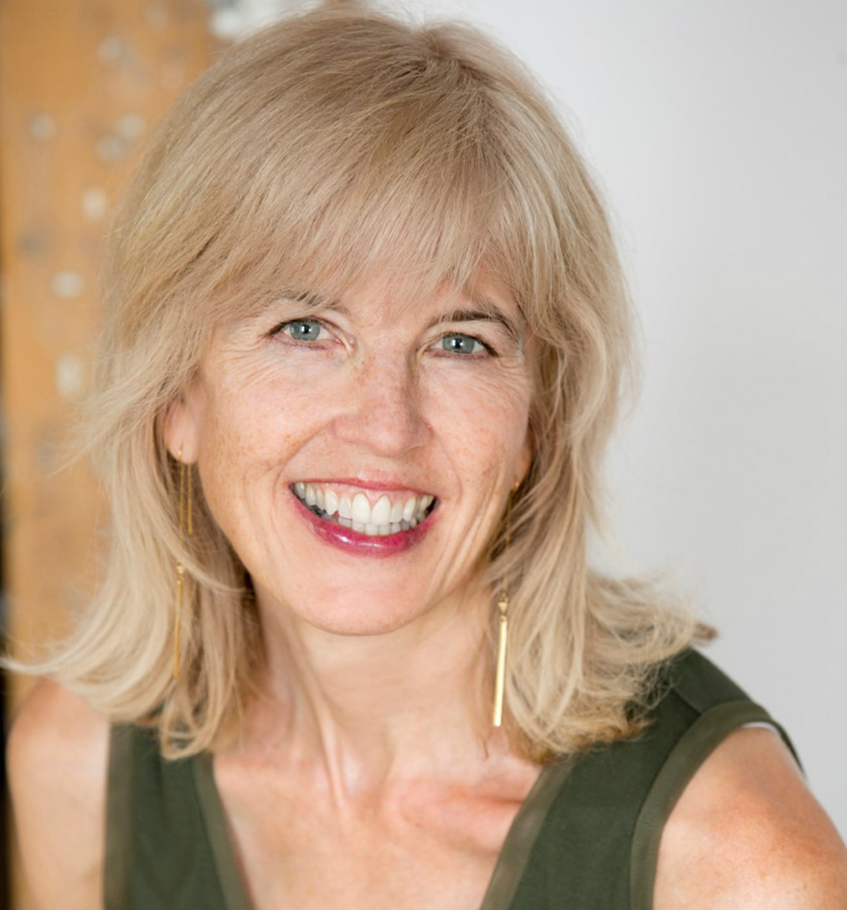 Alison McGhee, a white writer with short, blond hair, smiles for the camera