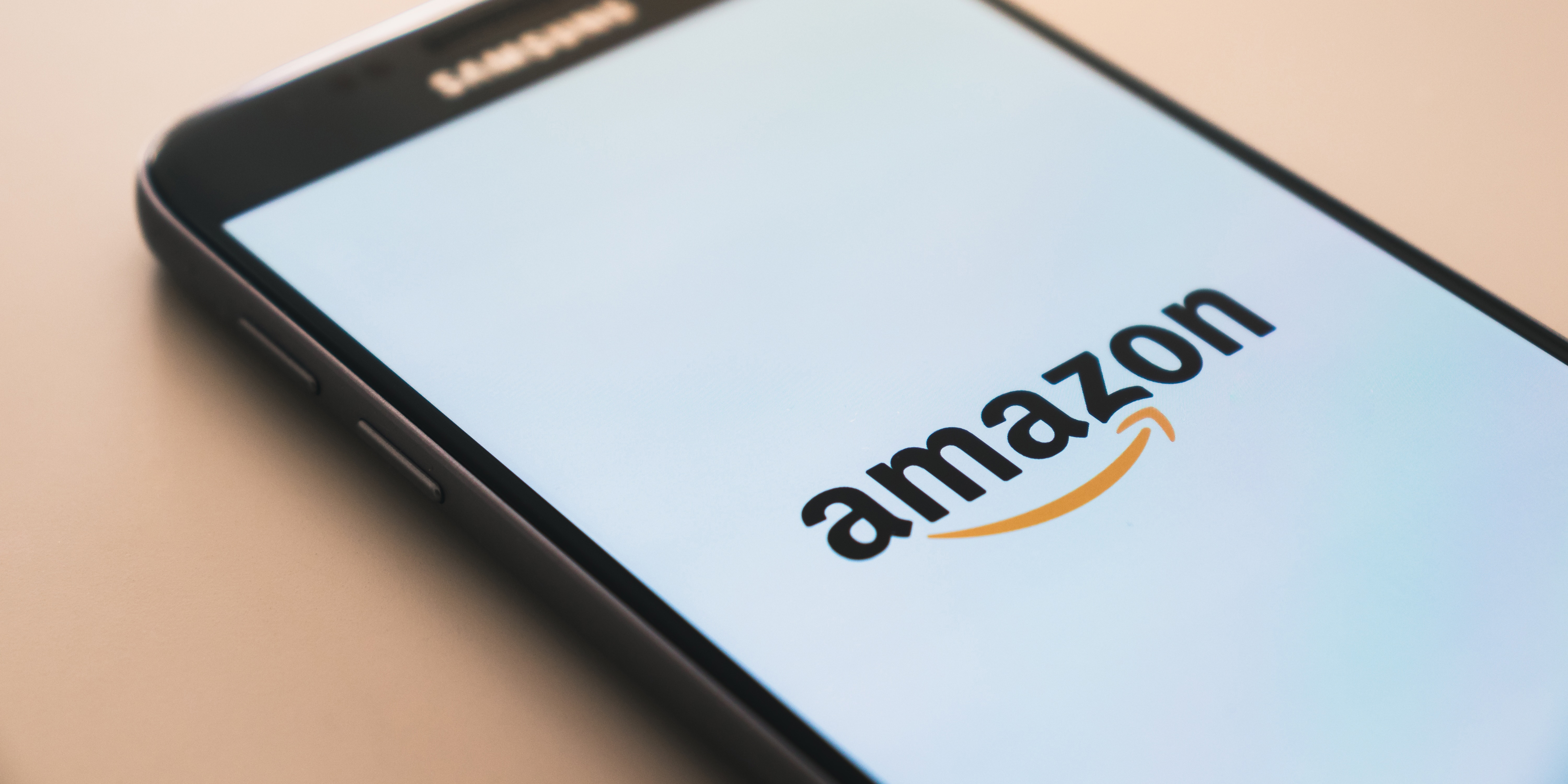 Amazon's logo on the screen of a black Samsung smart phone