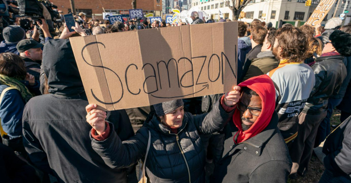 a group of protestors stand outside Amazon with Scamazon written on brown cardboard