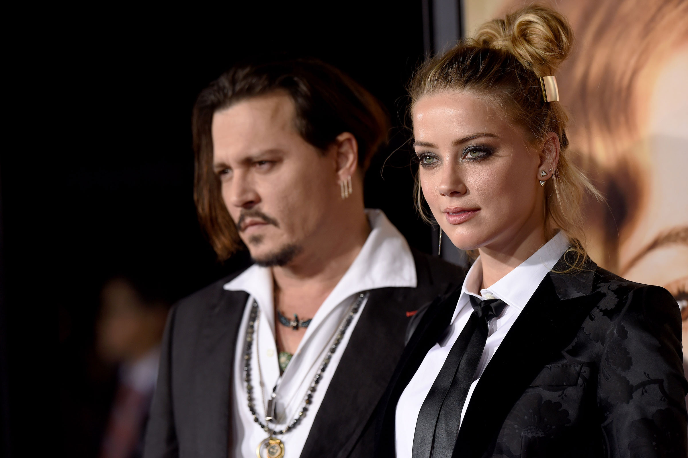 Amber Heard and Johnny Depp, a white couple both wearing all black outfits, pose together on a red carpet in 2015