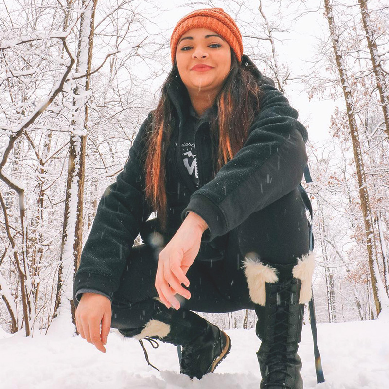 Photo of brown woman crouching in a snowy forest, wearing outdoor winter clothes and smiling at the camera