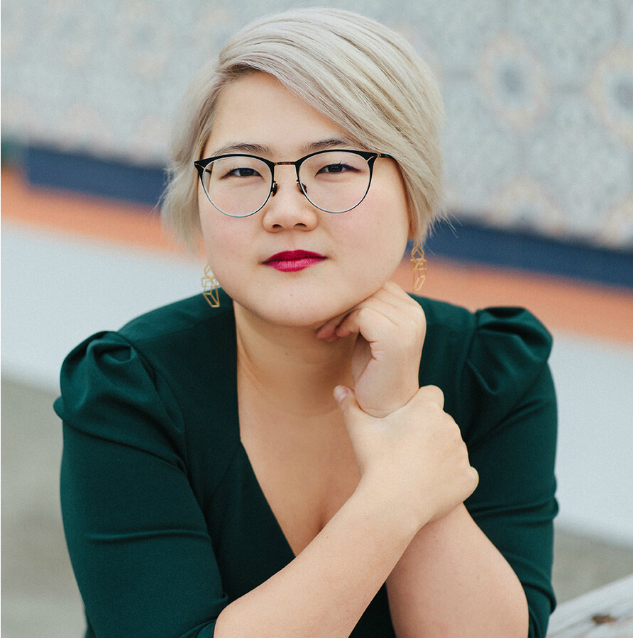 A photo of Angela Chen, who has white-blond hair, glasses, and red lipstick and wears a dark green dress.