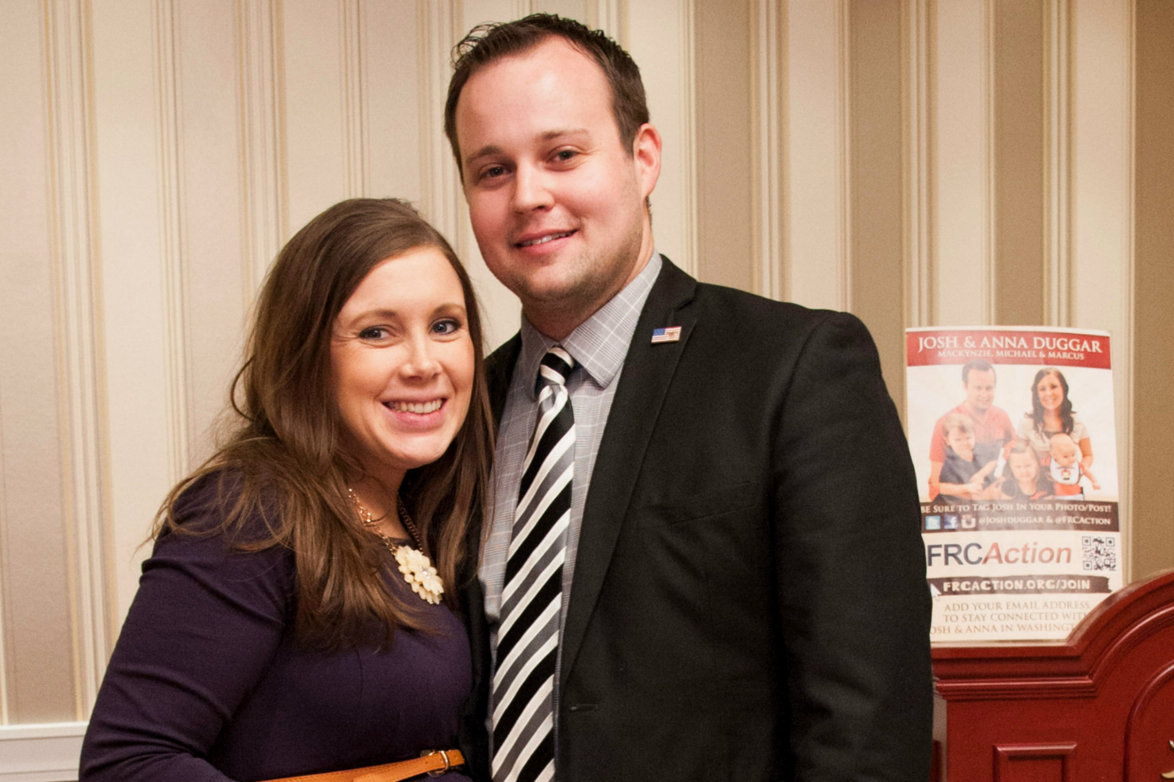 Anna Duggar, a white woman with shoulder-length brown hair and wearing a purple dress, poses with her husband, Josh Duggar, a white man wearing a black suit