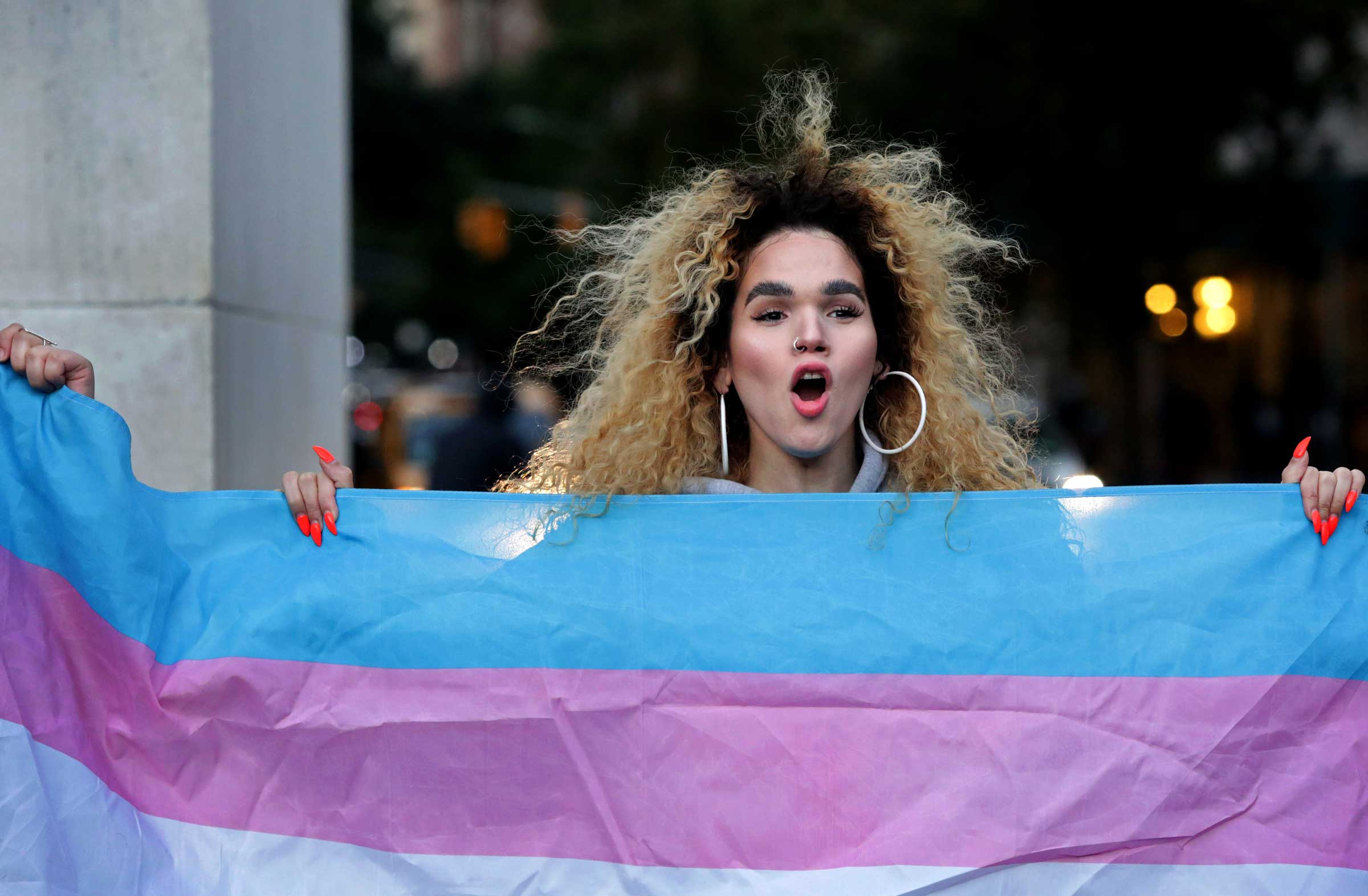 a brownskinned woman with a blond afro holds the transgender flag at a rally in New York