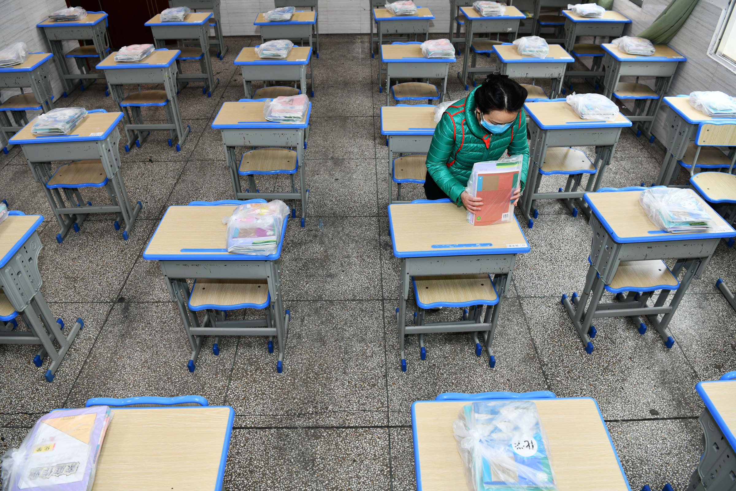 A teacher puts new textbooks on desks in advance for students of grade nine at a school.