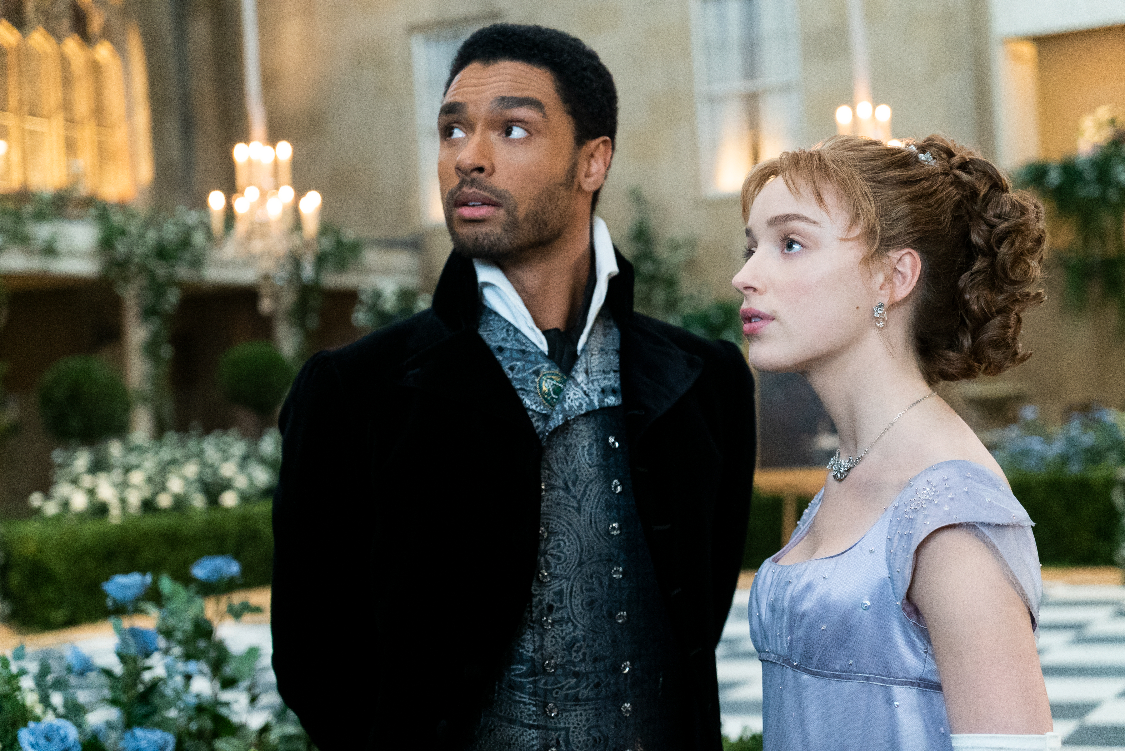 A white woman and a Black man walk together into a party. Both are dressed up in Regency-era clothing.