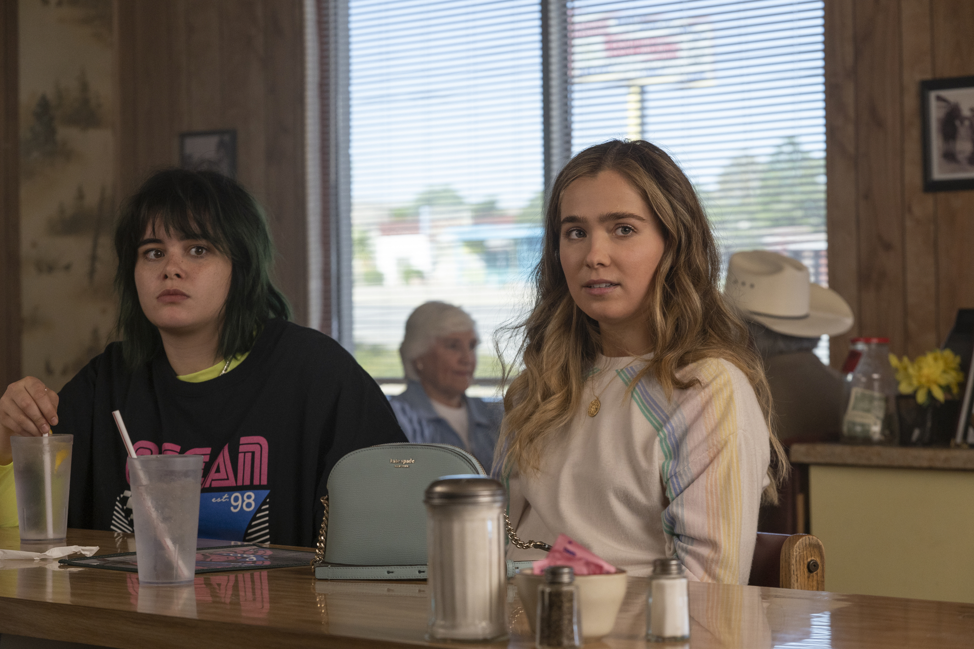 Barbie Ferreira, a white woman with short, multicolored hair, sits beside Haley Lu Richardson, a white woman with long, blond, curly hair, at a diner in Unpregnant