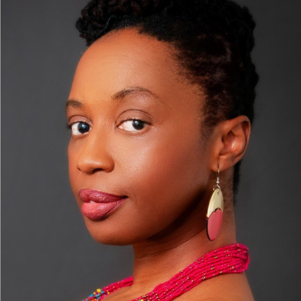 A photo of author Author Bassey Ikpi, a Black woman. She looks at the camera with a soft smile and has a colorful necklace and bright earrings.