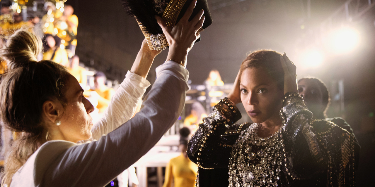 Beyonce backstage pulling her hair back as an assistant holds up a Nefertiti crown to place on her head. She is wearing a lavish costume covered in jewels and gold baubles.