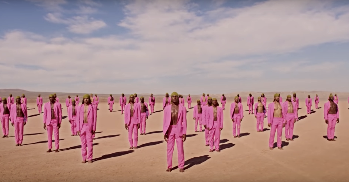 "A photo from Beyoncé's ""Spirit"" music video. A large group of Black men wear pink outfits and olive-colored durags in the desert."