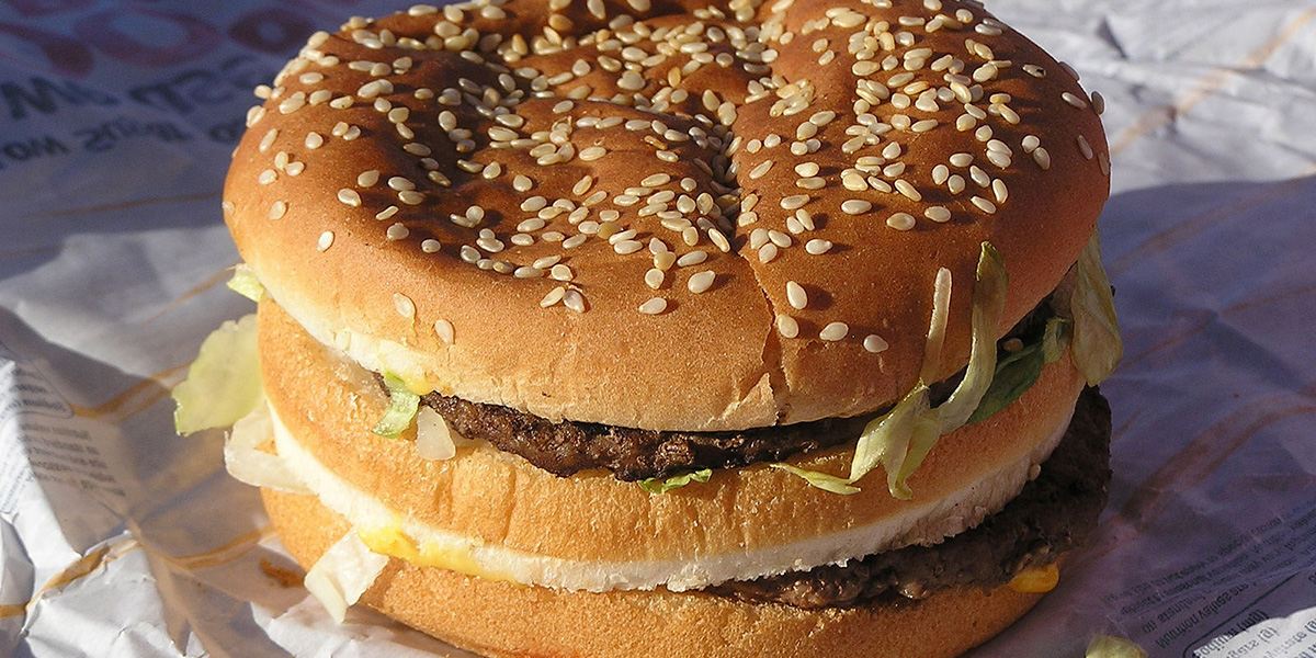 Closeup of a Big Mac cheeseburger on top of a McDonalds wrapper