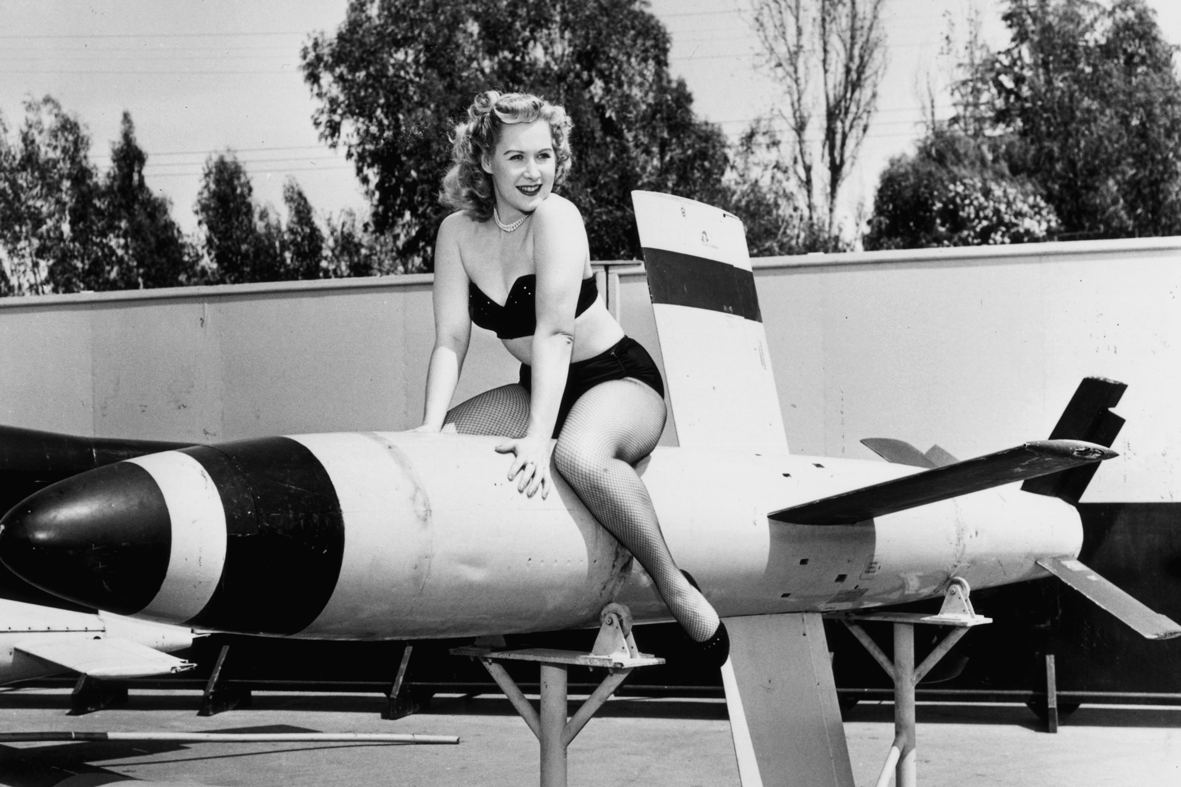 Joy Healy, a white, blond, thin woman sits on top of a missile while wearing a bikini