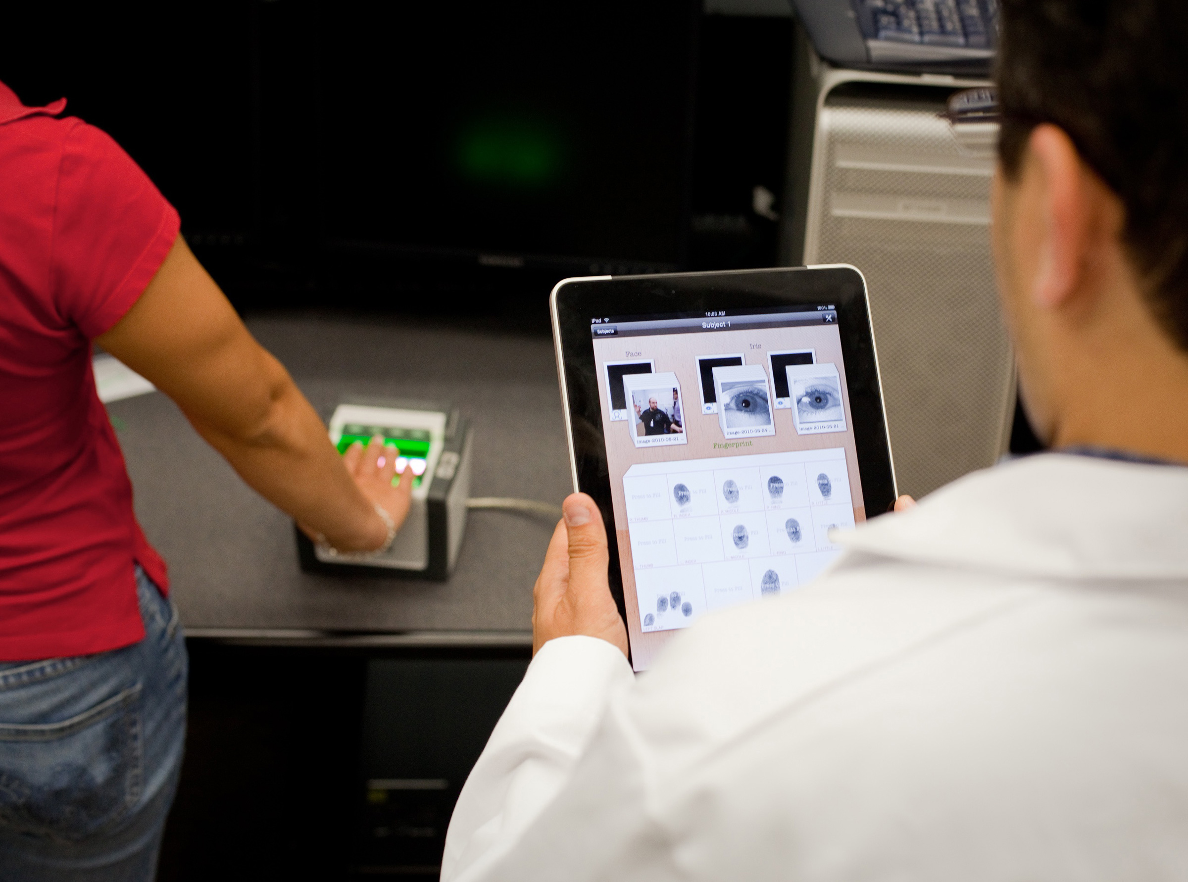 a white person holds a tablet that showcases the fingerprints of a woman of color whose hand is on top of a green scanner