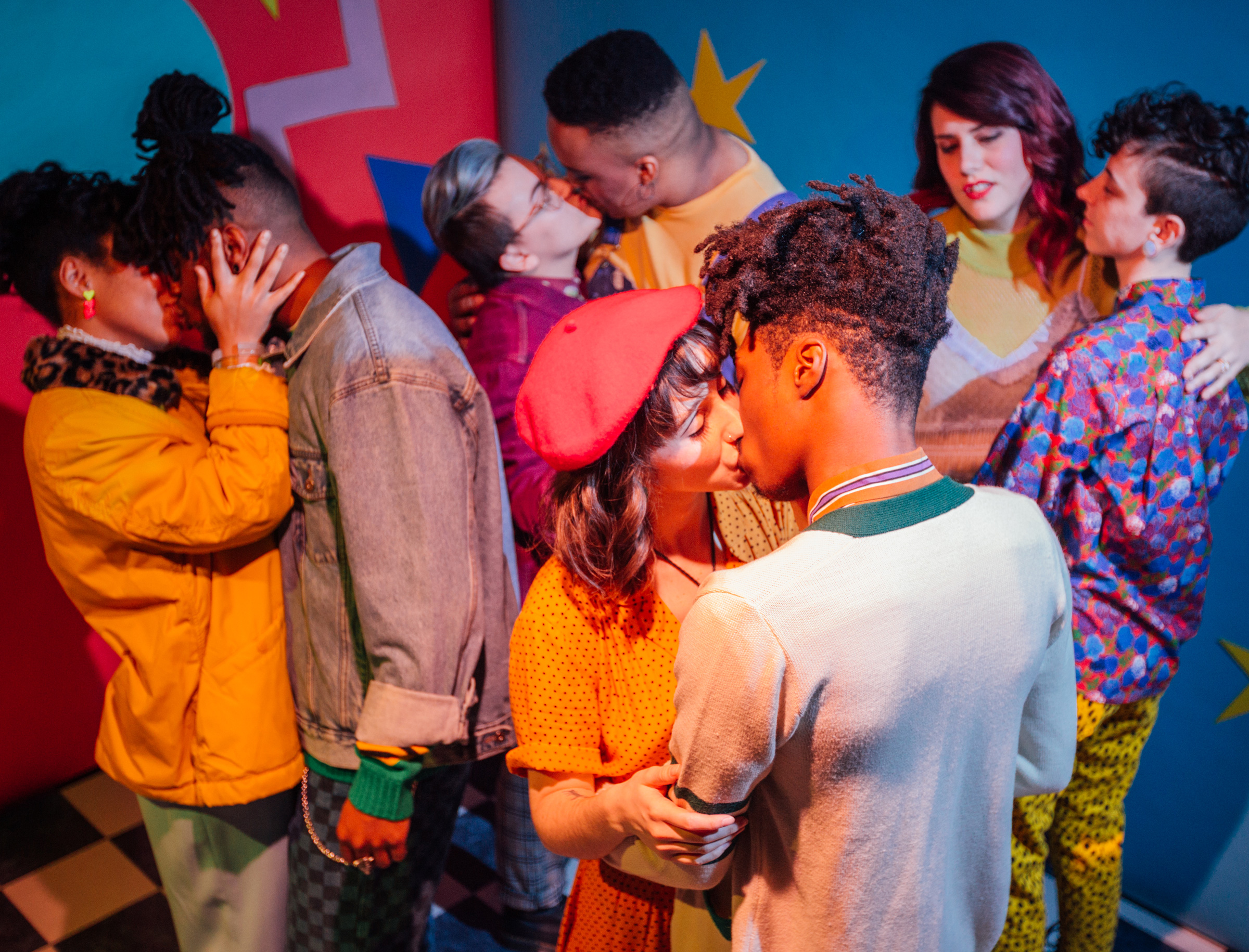 A colorful photo of several couples kissing and being affectionate.