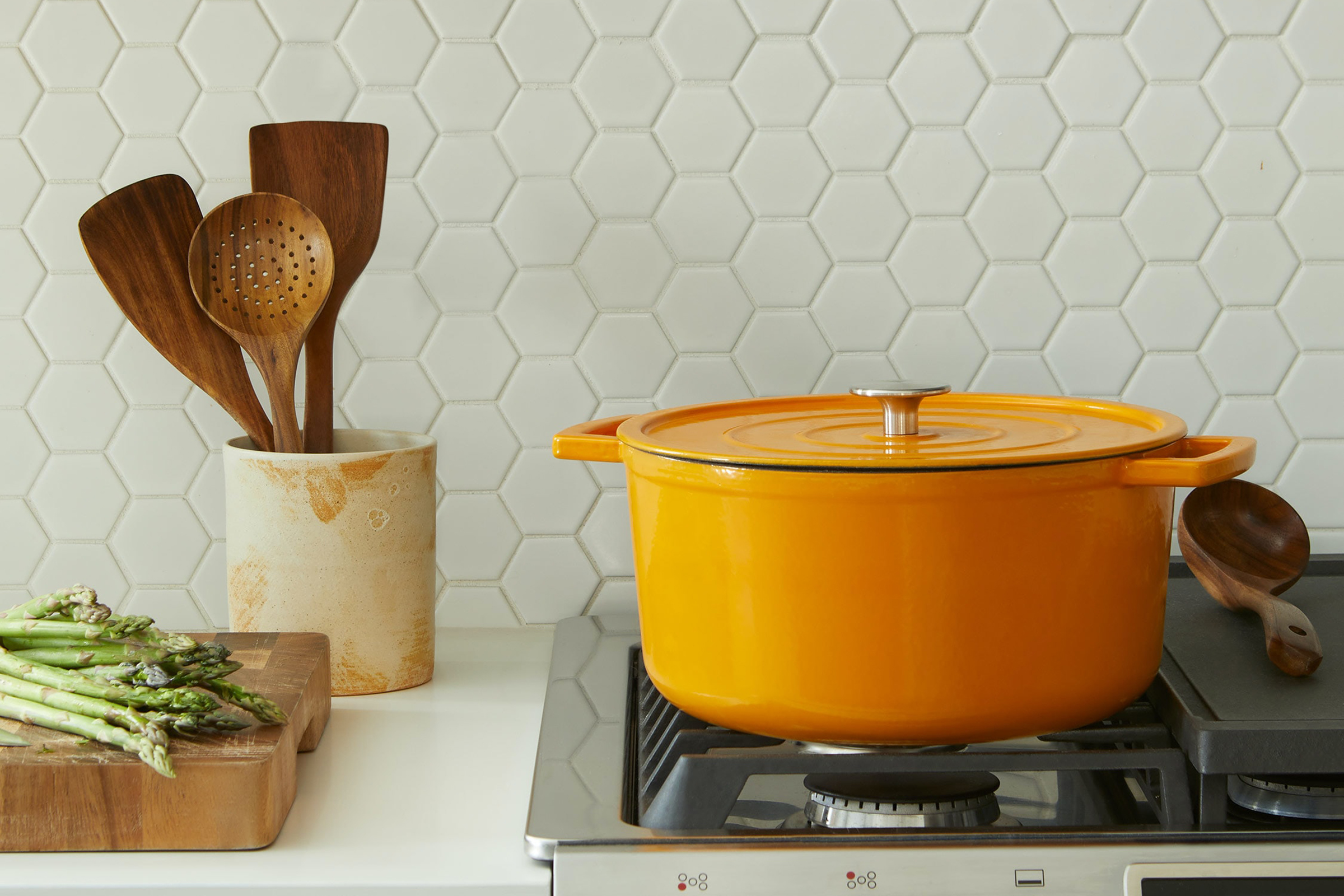A bright yellow dutch oven resting on top of a stove, on the counter next to it is chopped asparagus on a wood cutting board and a utensil holder