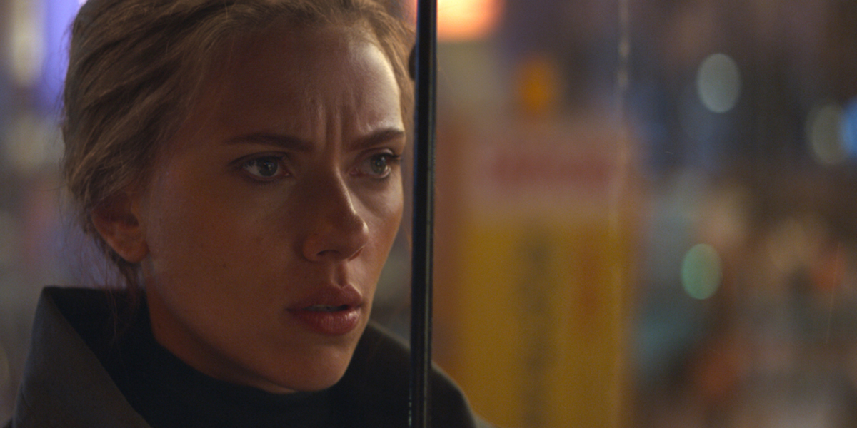 A close up of Scarlett Johansson with a concerned look on her face and a blurred background