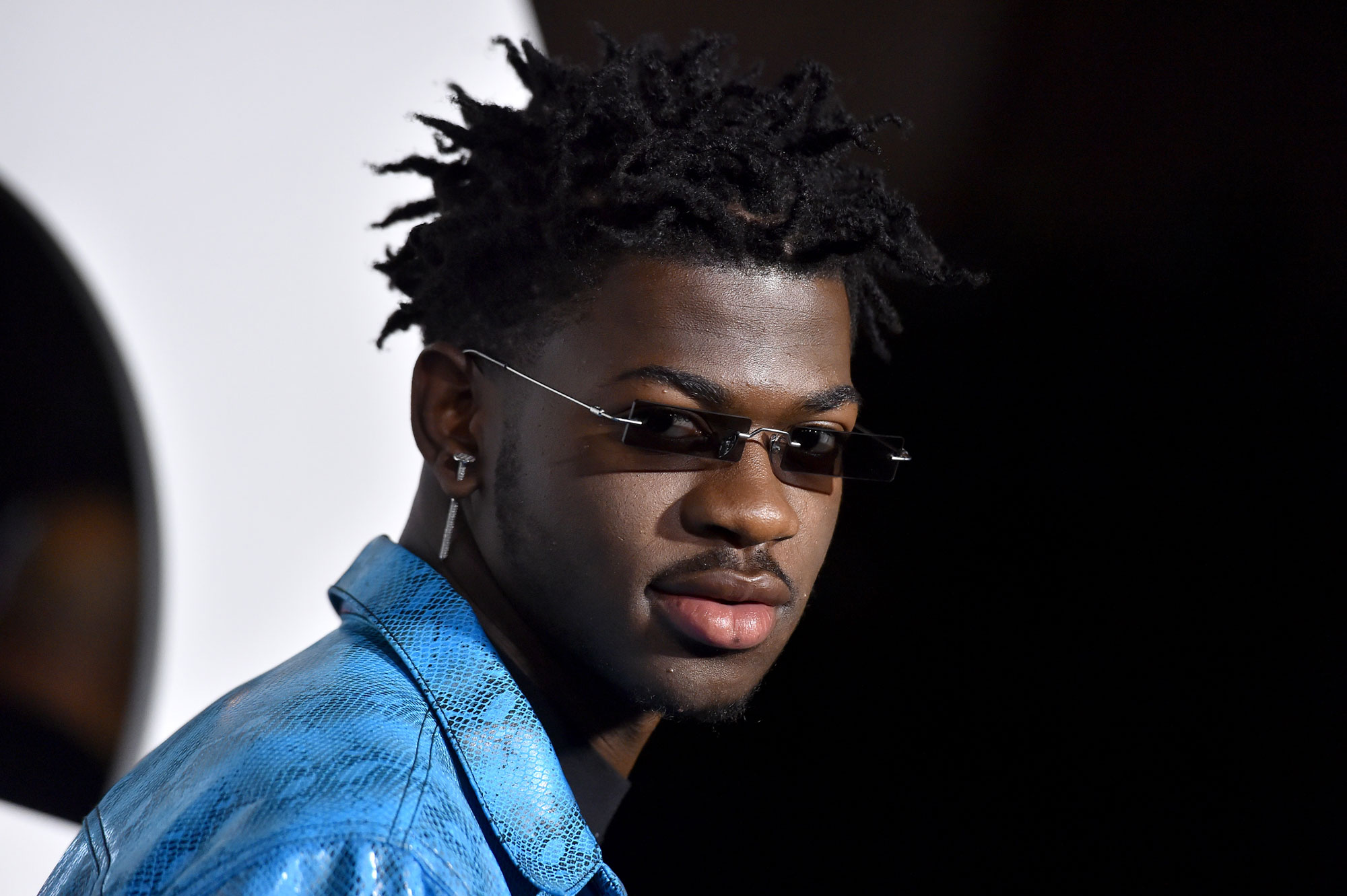 Lil Nas X, a Black man, wears a blue snakeskin jacket, a long earring, and vintage sunglasses.