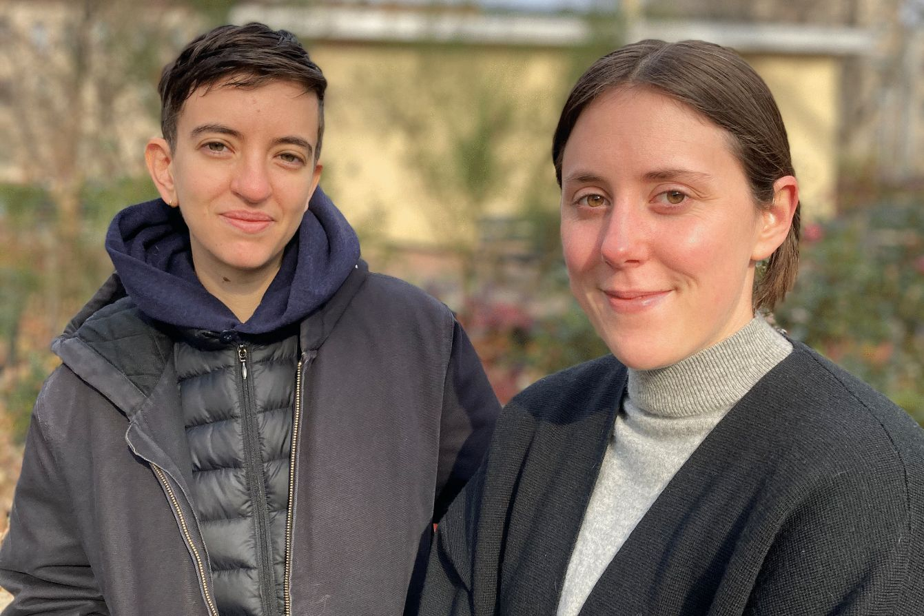 Eve Gleichman, a thin white person with short brown hair, stands outside and beside Laura Blackett, a white person with neck-length brown hair