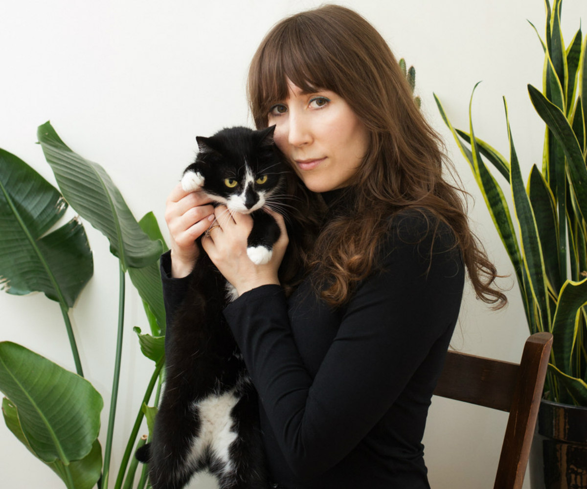 """Girls and Their Cats"" author BriAnne Wills, a white woman with dark hair, holds her cat, Tuck. There is a large plant in the background."
