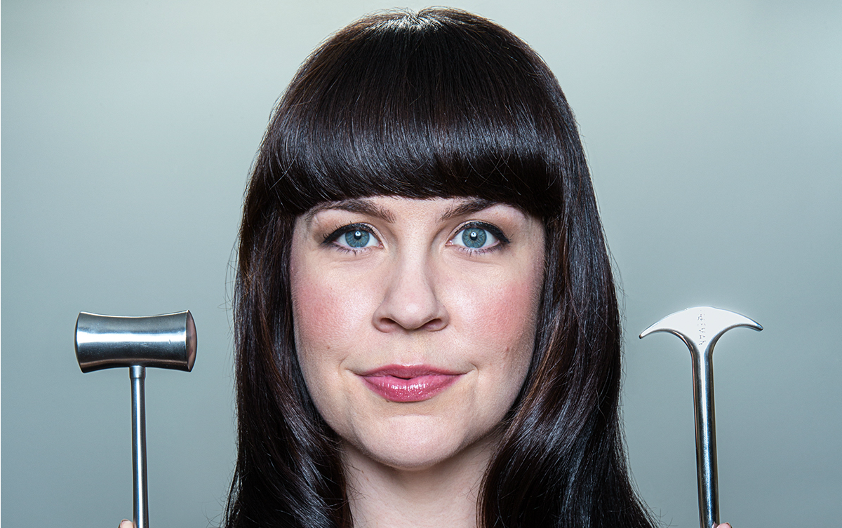 Caitlin Doughty, a pale, white woman, with long, black hair, holds death tools in her hand