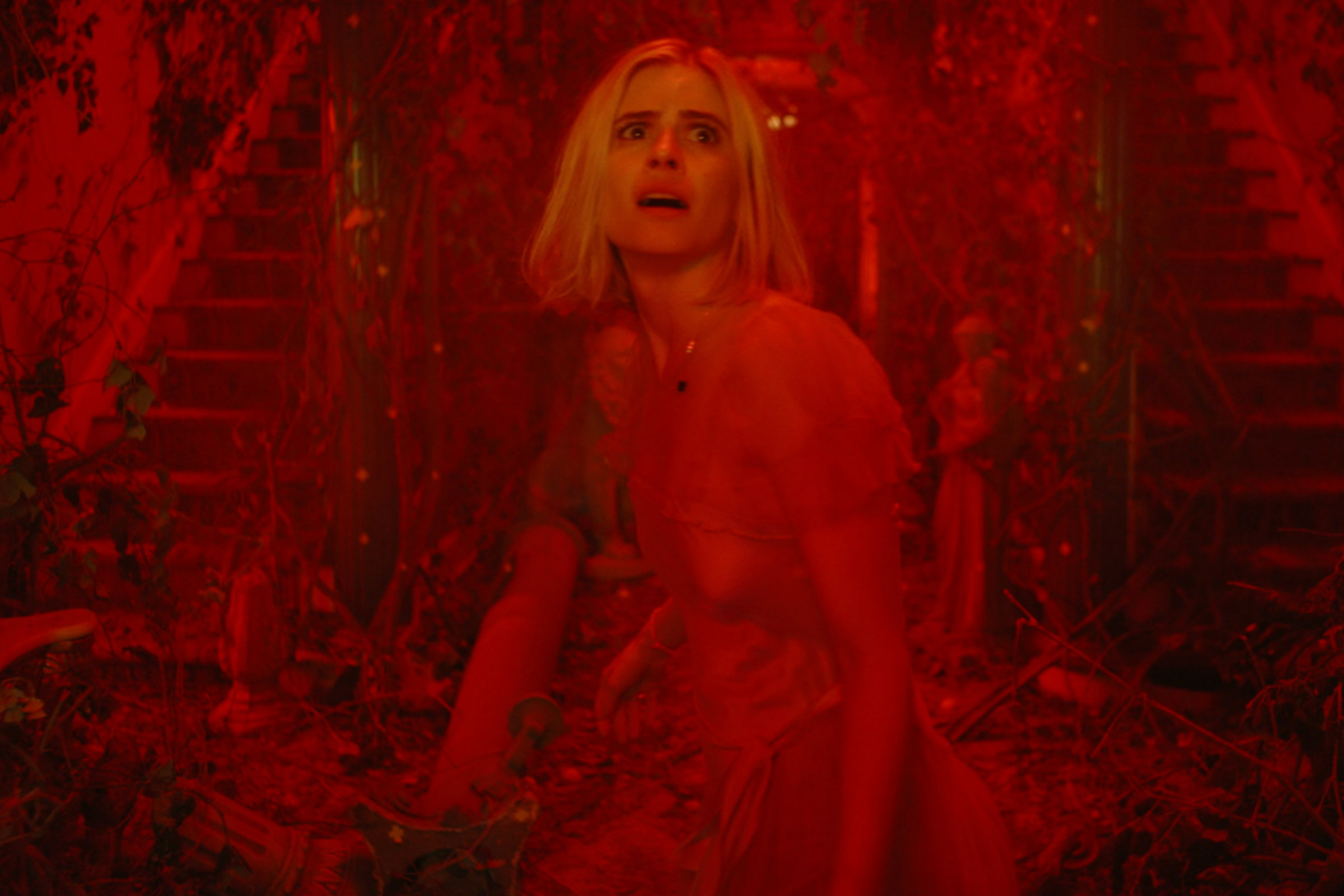 Carlson Young plays Margaret, a white woman with short, blond hair, who looks aghast as she moves through a deep red world, in The Blazing World