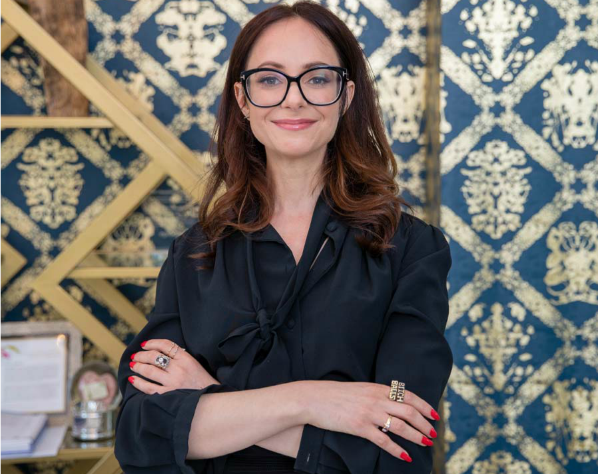 Carrie Goldberg, a lawyer dressed in a chic black shirt, glasses, and red lipstick, stands in front of a printed background with her arms folded