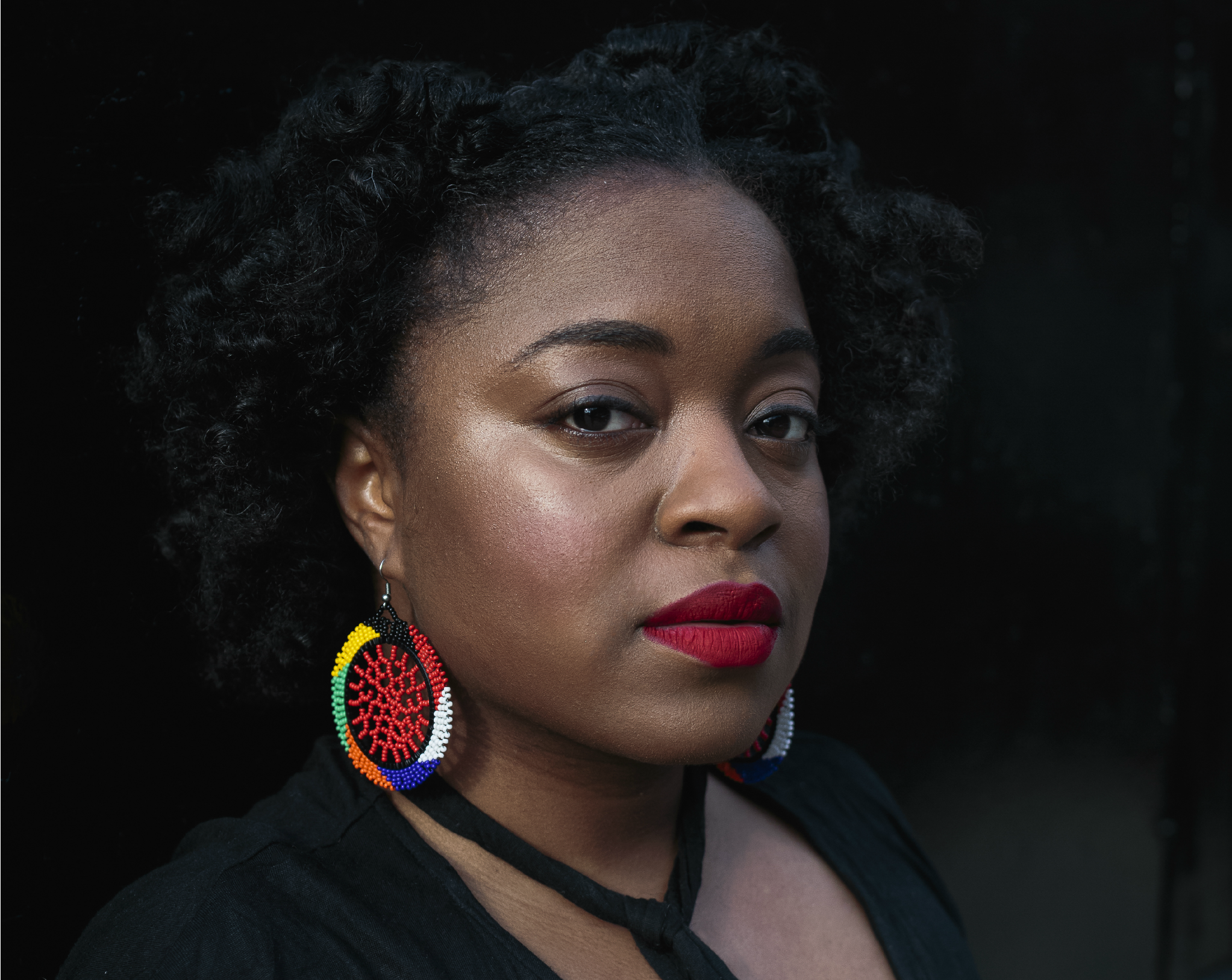 black woman with black curly hair, a black shirt, and red, yellow, green, white, and blue circle earrings and red lipstick looking at the camera