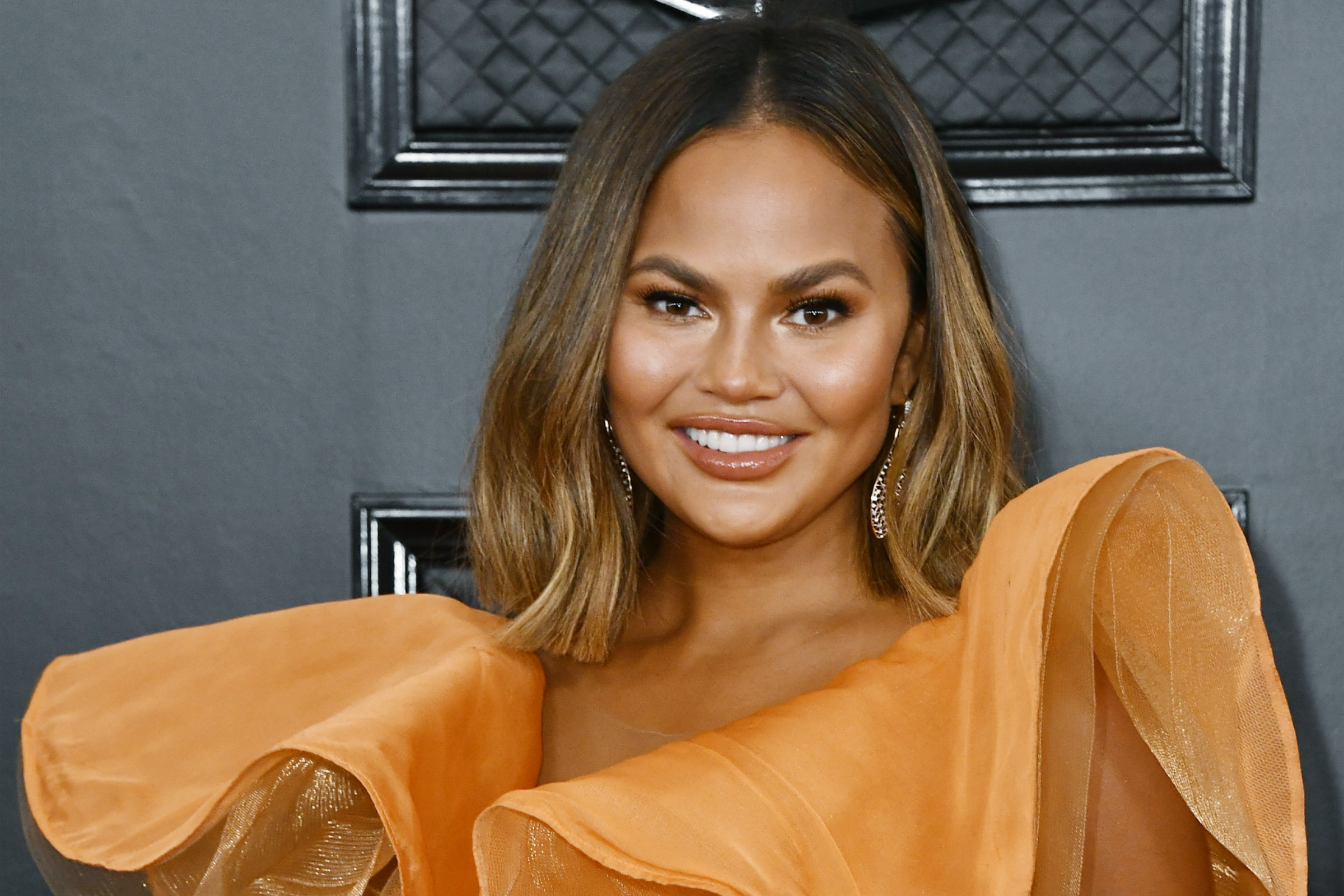 Chrissy Teigen, an Asian woman with blond-brown hair, smiles on the red carpet in a bright orange dress