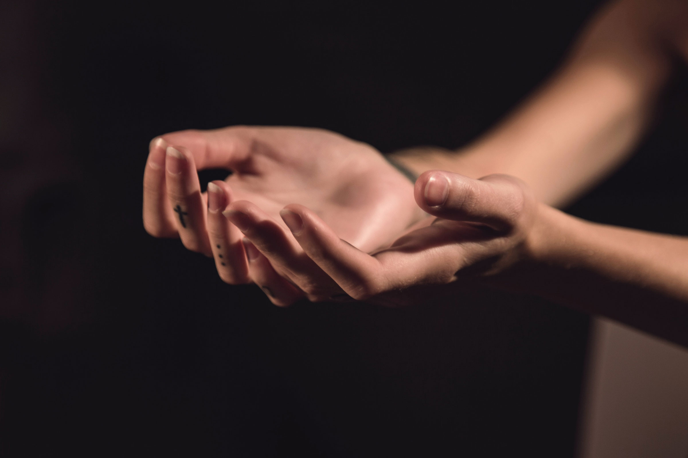 a white hand with a cross tattoo on her middle finger are posed against a black background
