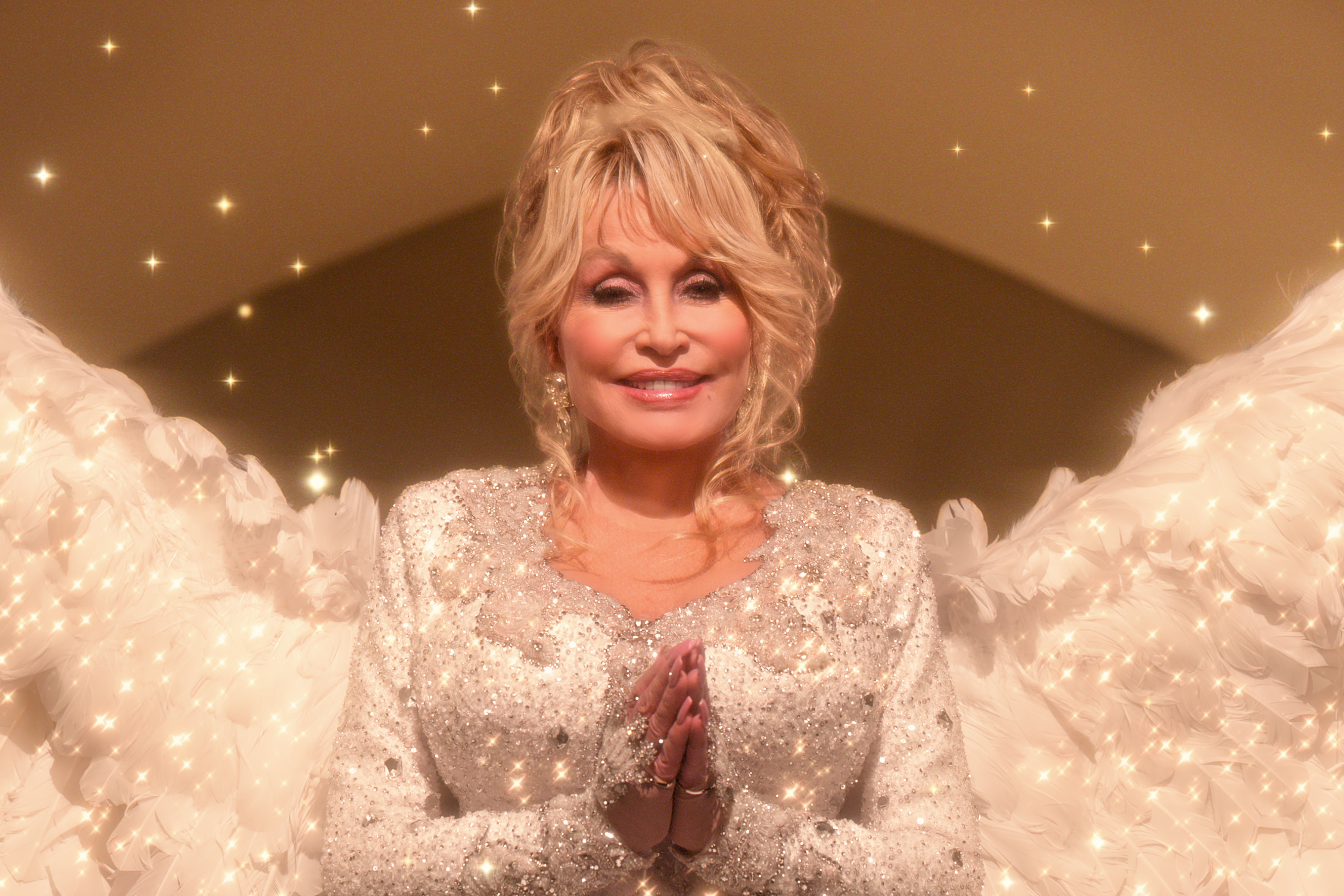 Dolly Parton, who is white with blond hair, is glowing and wears a glittery gown.