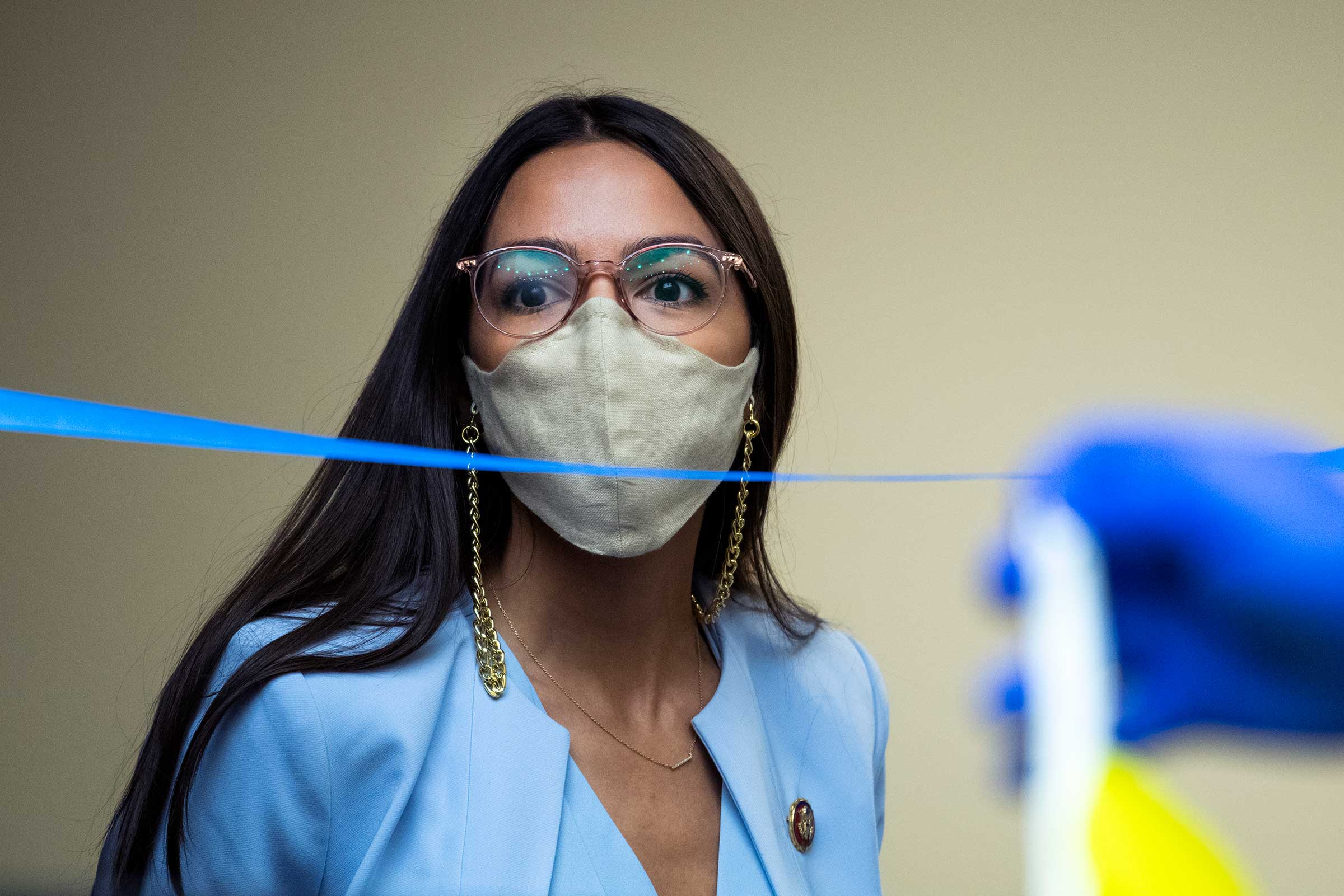 Alexandria Ocasio-Cortez, a Latinx woman with long, black hair, and wearing glasses, has a gray mask over her face