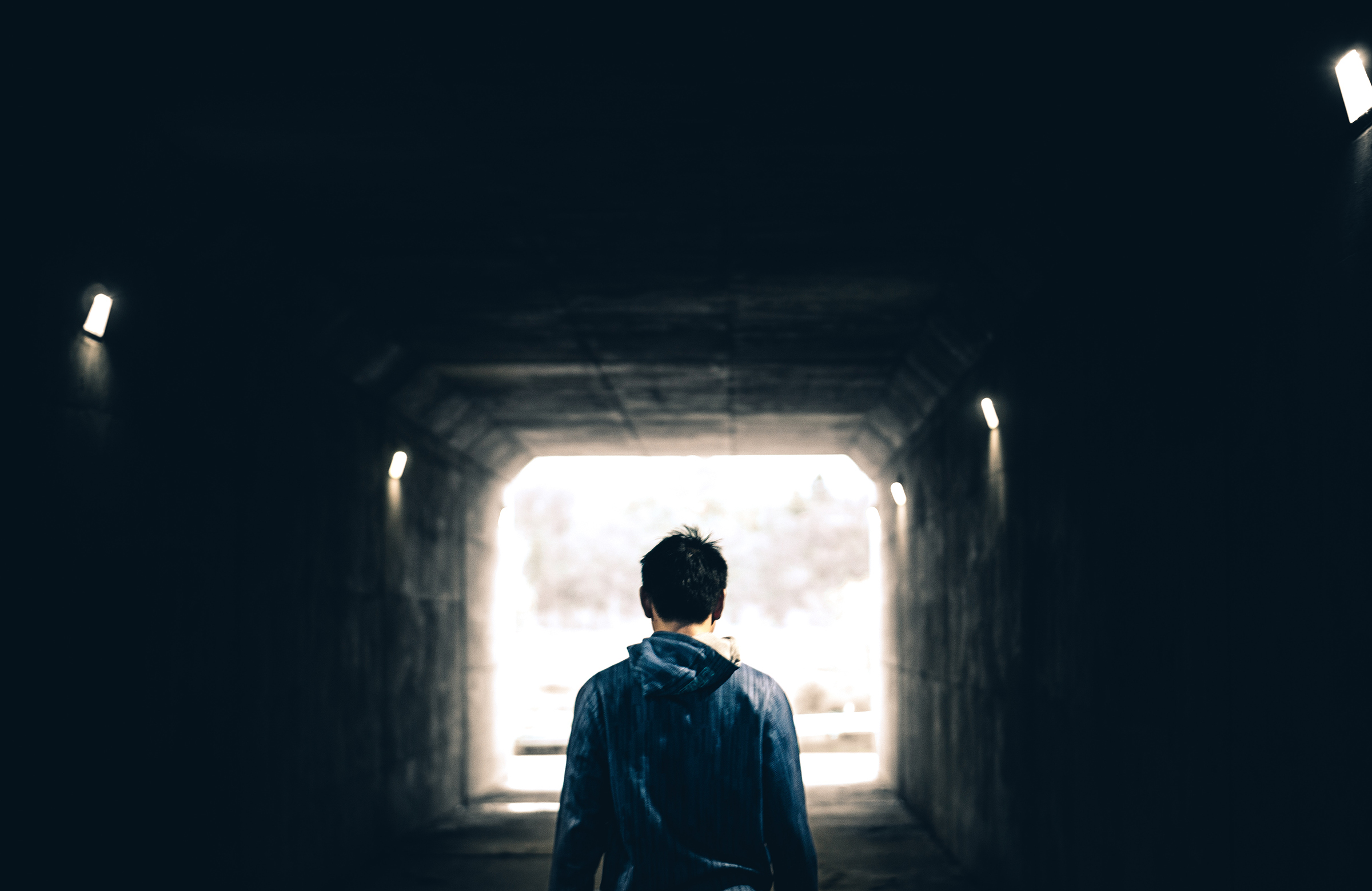 a photo of the back of a white man walking into a tunnel