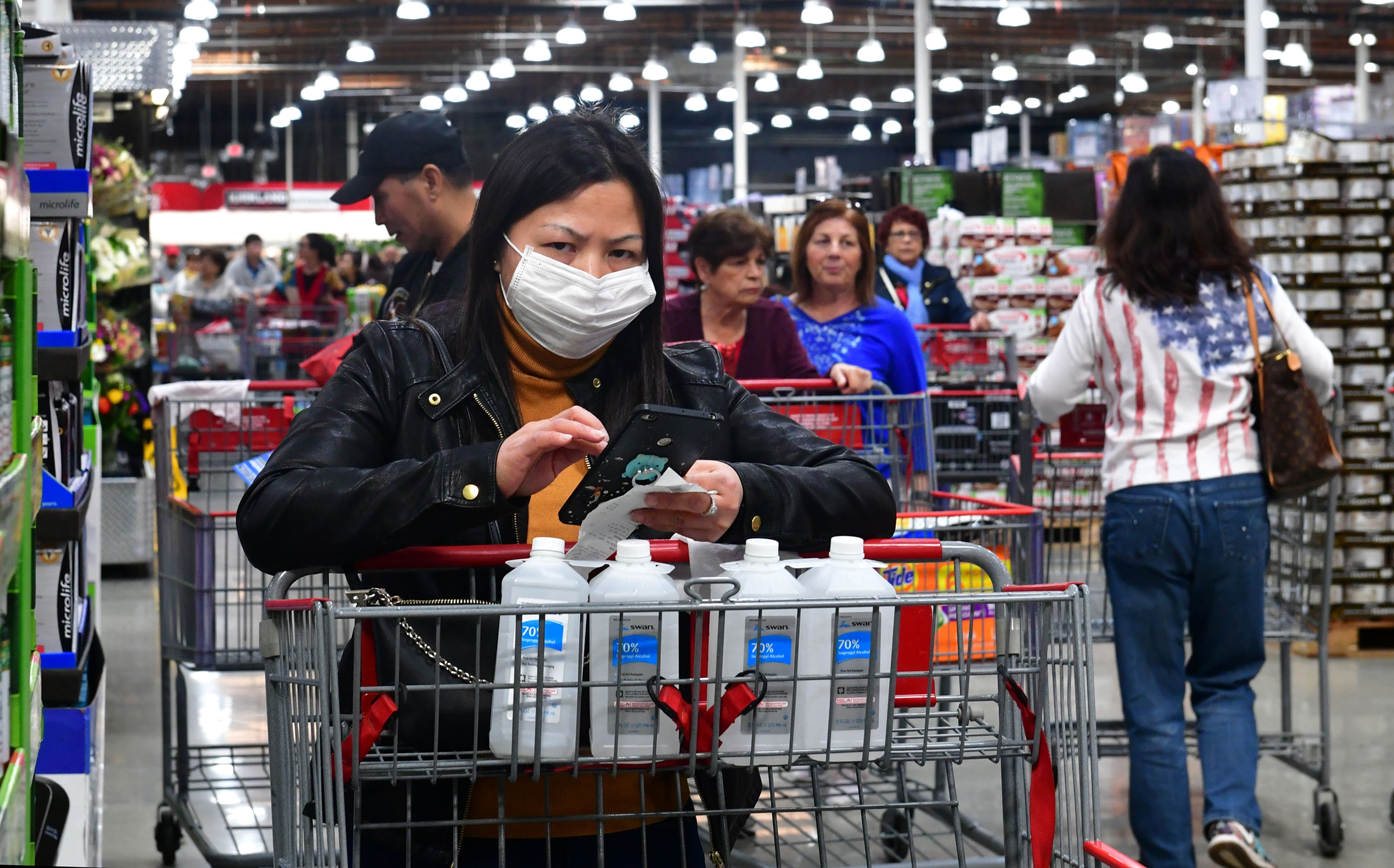 A woman wears a face mask while purchasing bottles of rubbing alcohol at a Costco store.