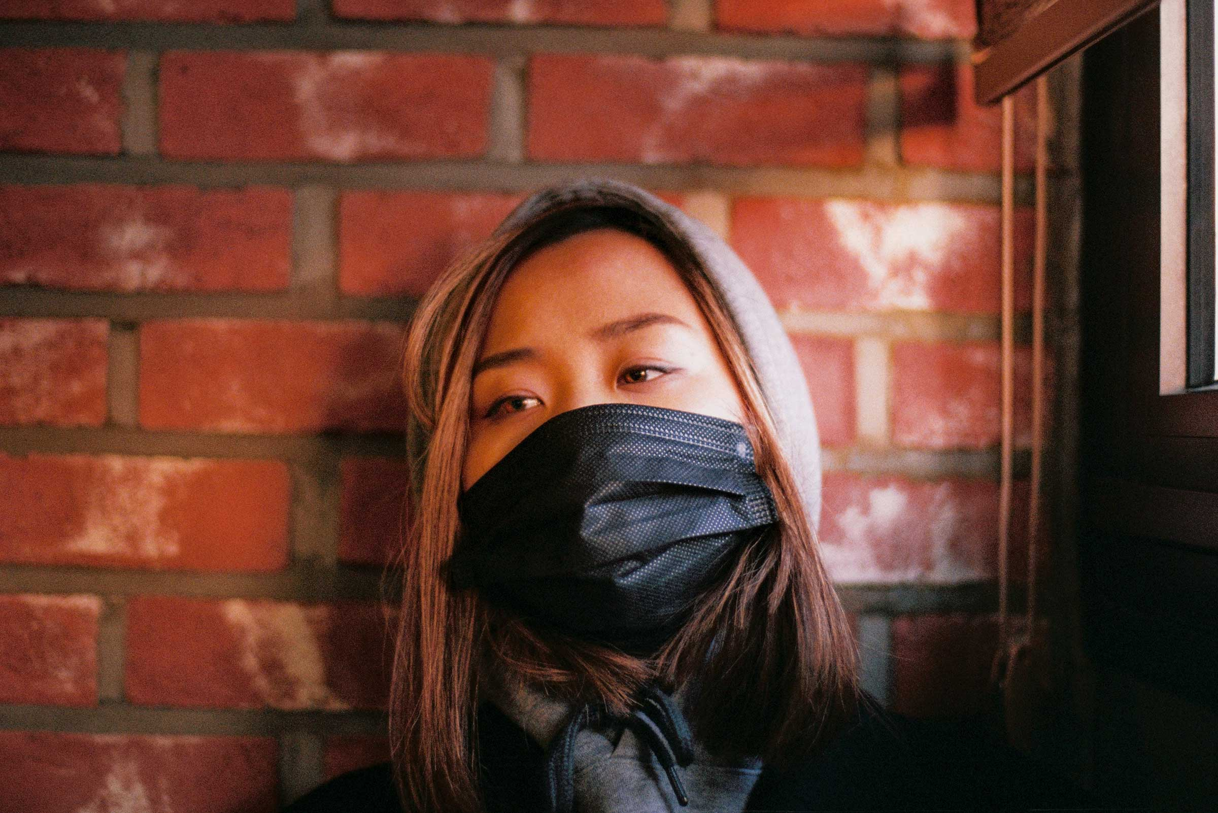 an Asian woman with shoulder-length blond hair is wearing a black mask across her face as she stares into space