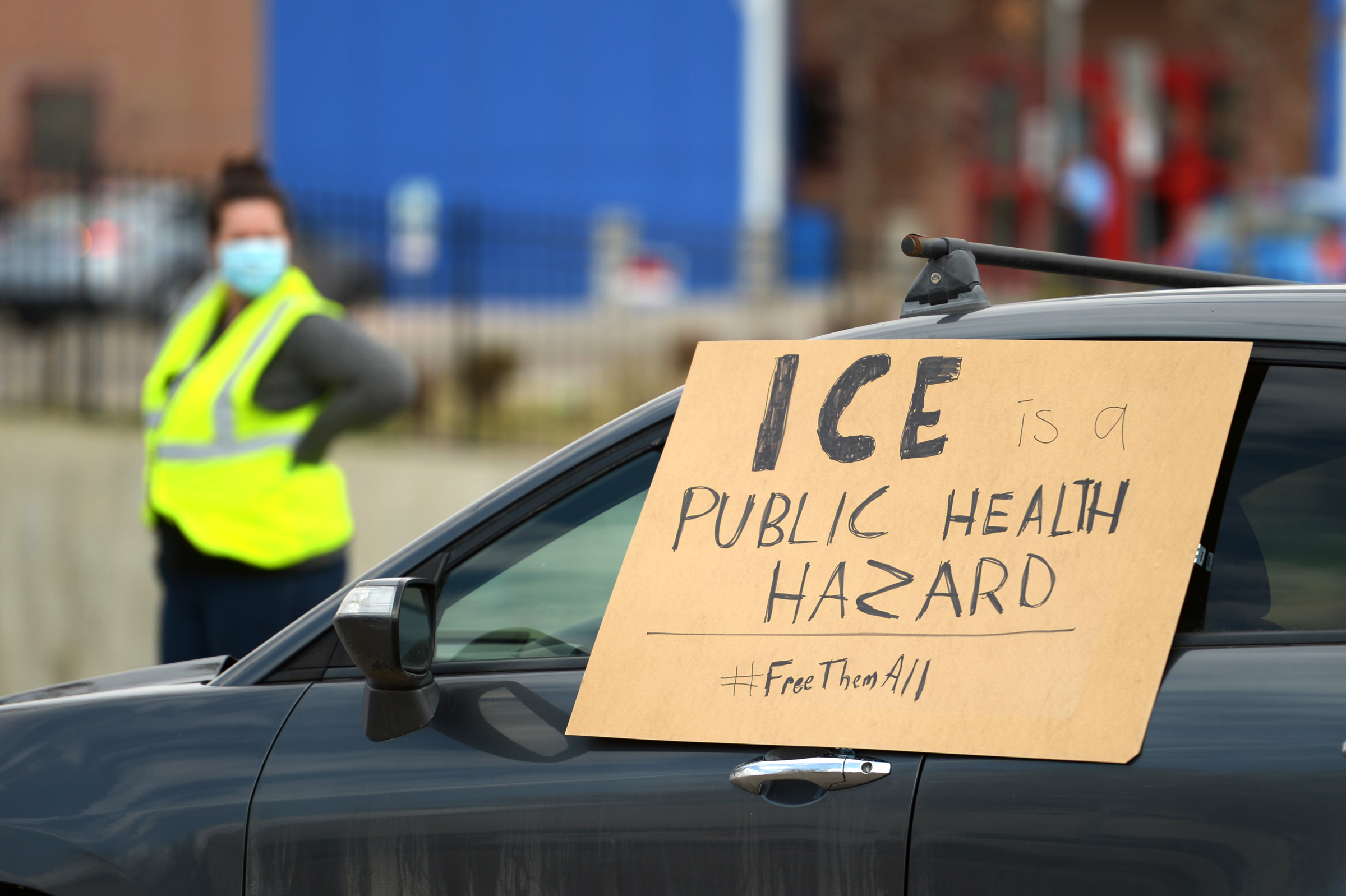 a caravan of cars hold signs in front of an ICE facility in Colorado to encourage the release of migrants
