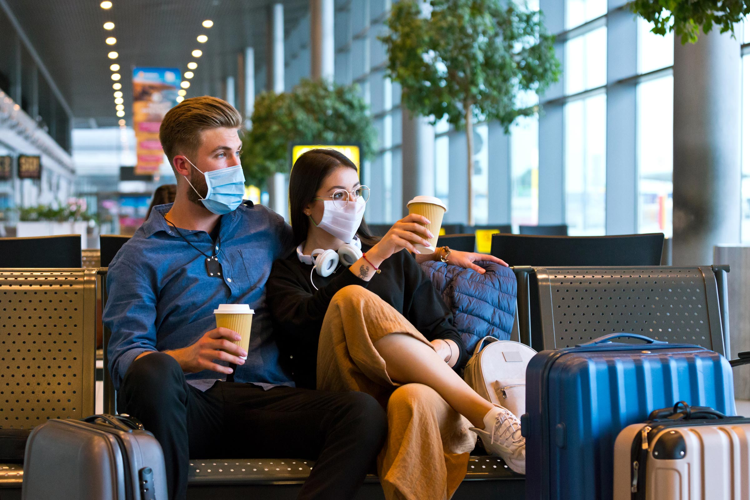 a young couple holding coffee cups sit together in the airport while wearing N95 masks