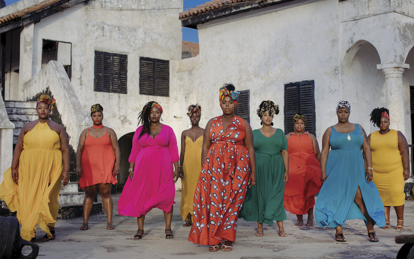 Nine Black women in various colors of dresses stand in front of Elmina slave castle on their trip to Ghana
