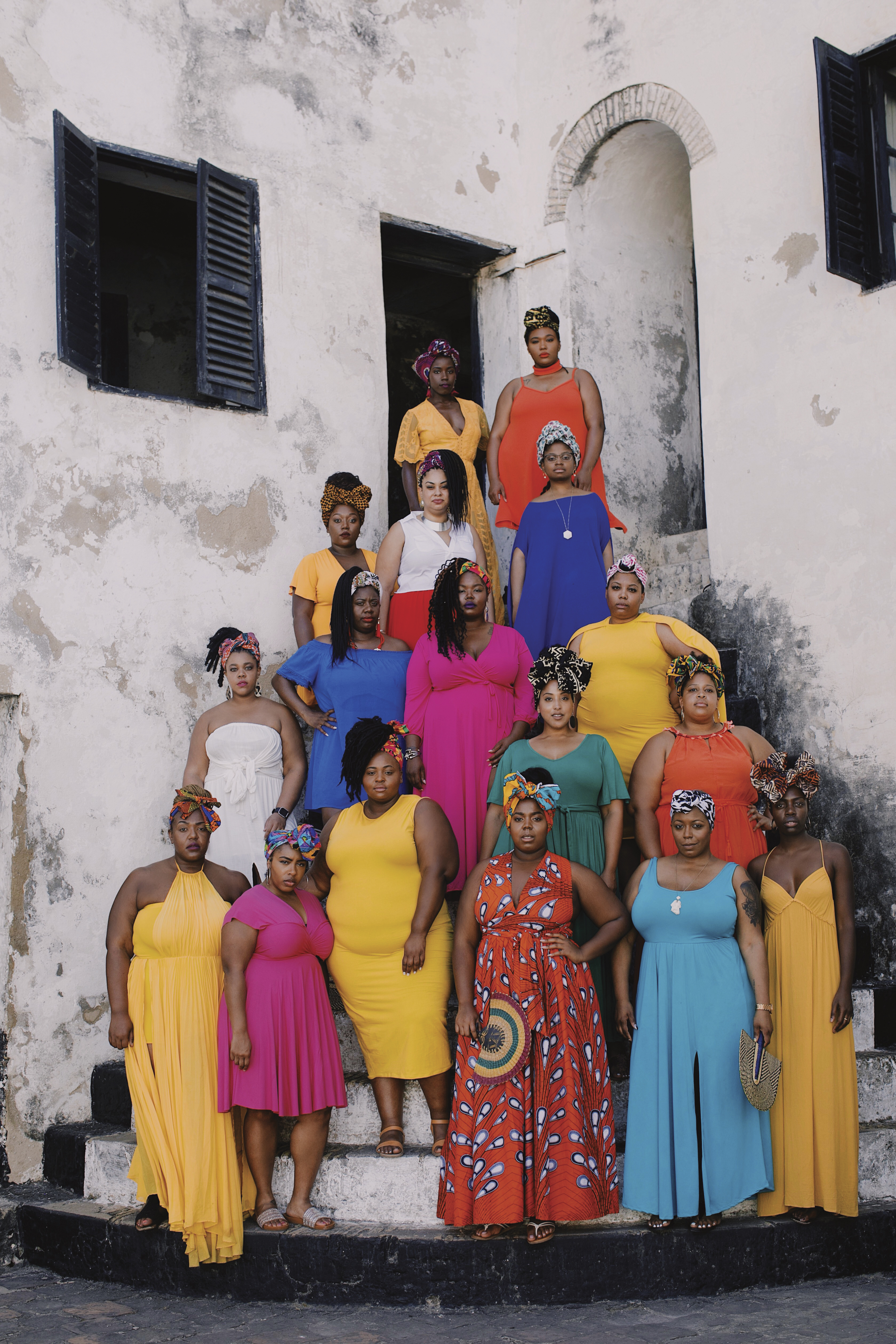Seventeen Black women in colorful dresses and headwraps stand in front of Elmina slave castle on their trip to Ghana