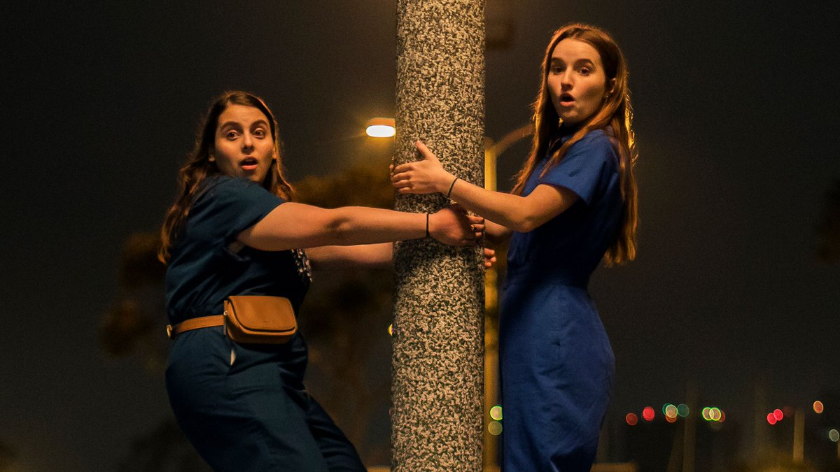 two white girls in matching blue coveralls cling to a lamp post