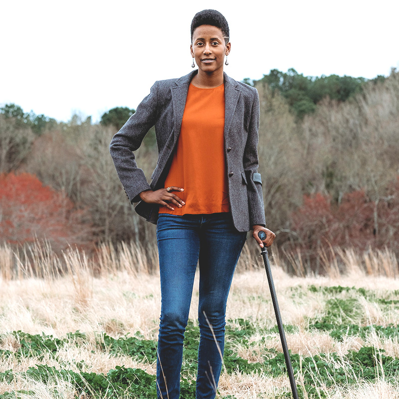Photo of a tall Black woman with short hair, wearing an orange shirt, gray blazer, and jeans, standing with a cane in the middle of a field