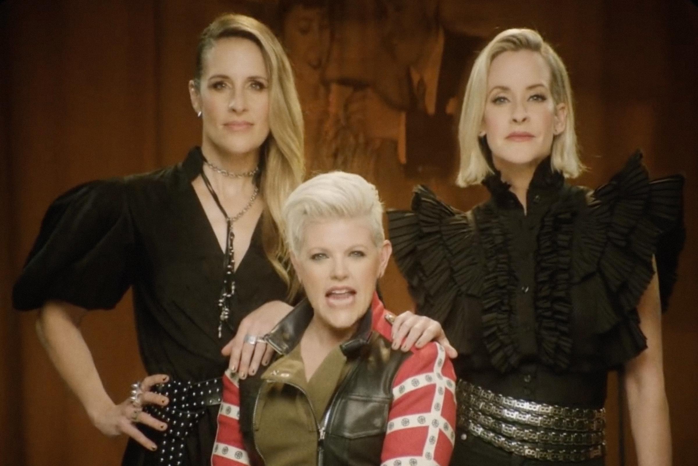 The Dixie Chicks, three white women, two with long hair, one with short hair, stand close together, their hands on each other's shoulders, each wearing bold, flamboyant clothing and an unapologetic look on their faces.