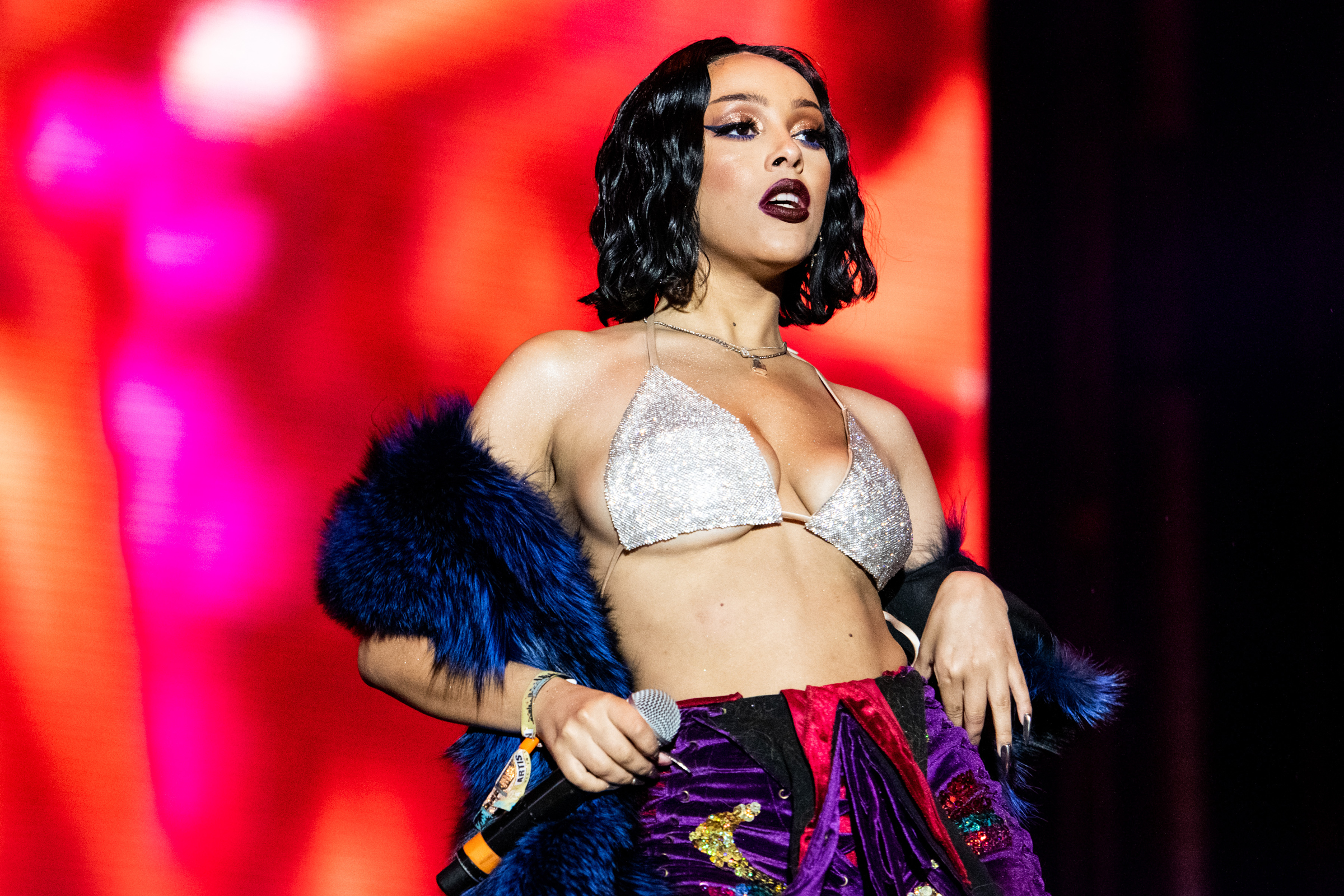 Doja Cat, a South African woman with short, brown hair, performs on stage in a red outfit