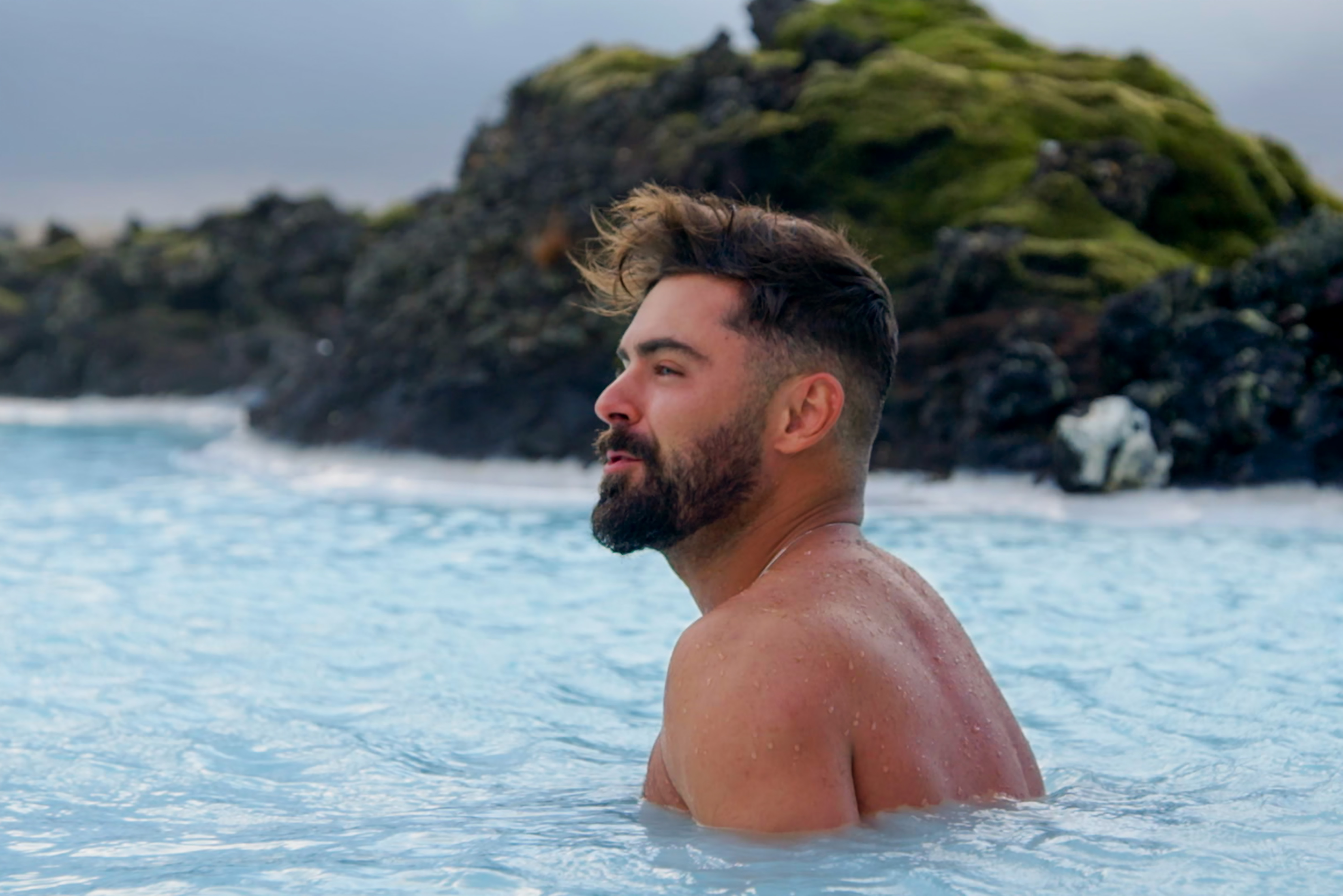 Zac Efron, a white man, is in a hot spring in Iceland.